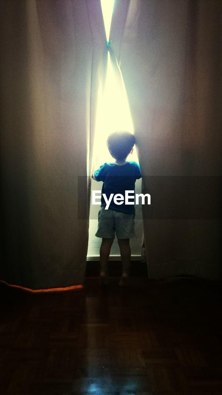 Rear view of boy peeking though house window