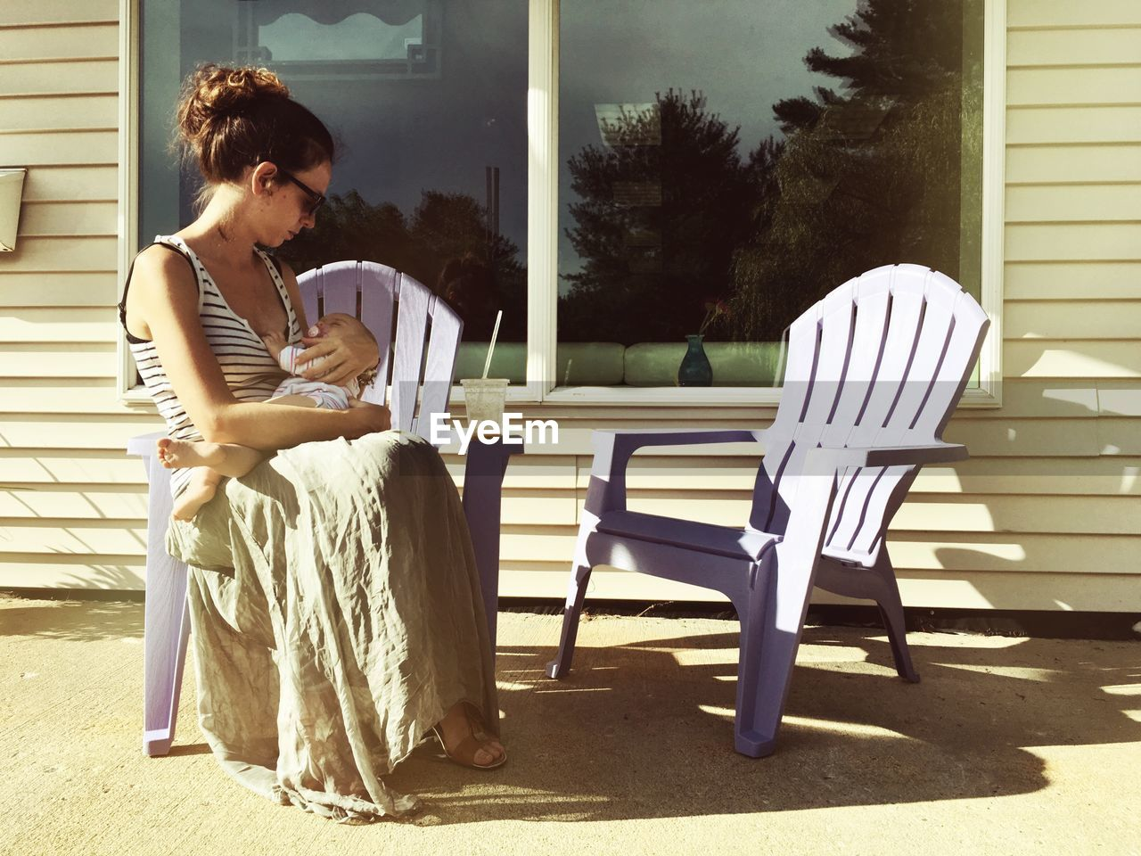 Woman with baby sitting on adirondack chair in back yard