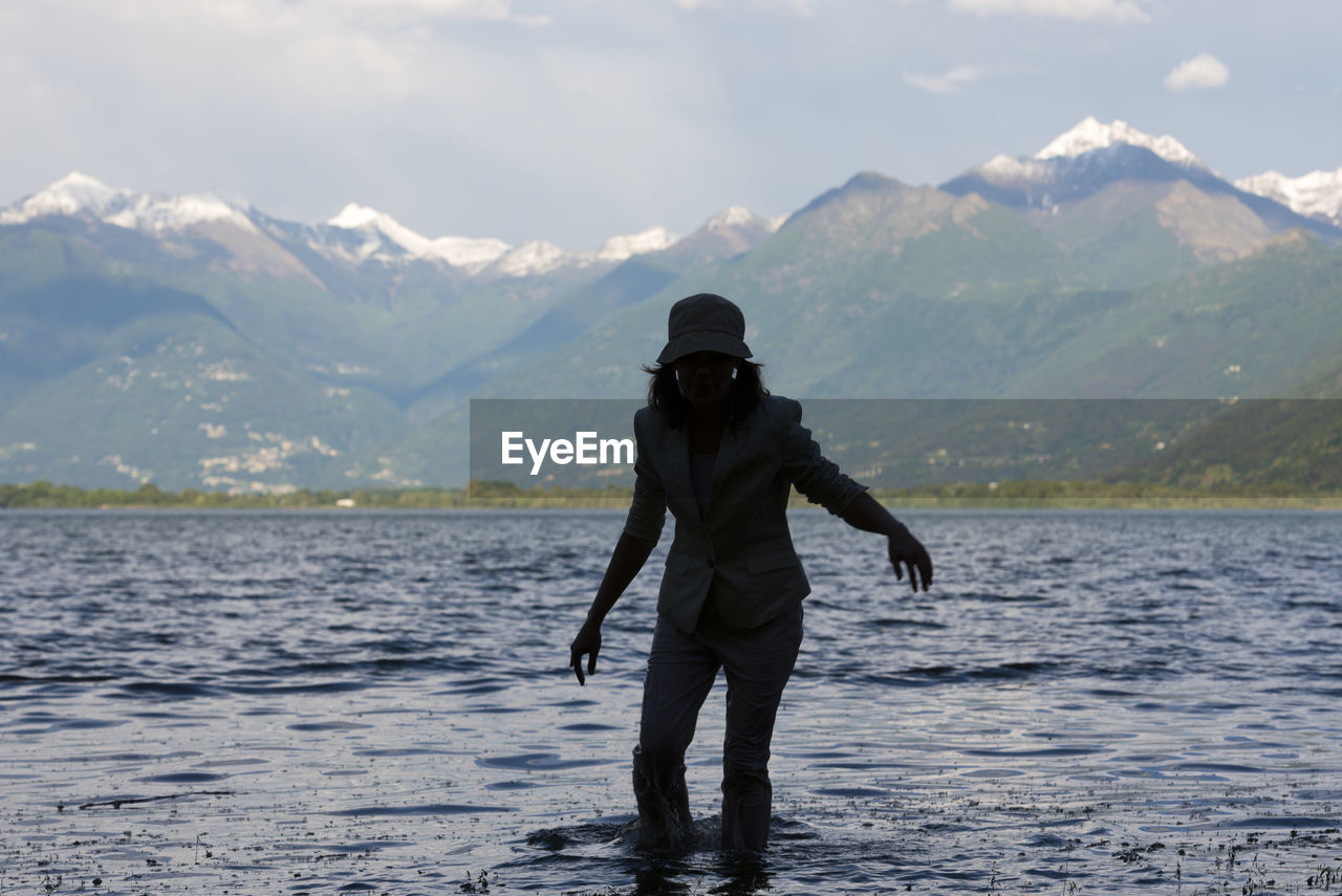 Woman Standing In Lake Maggiore Against Mountains