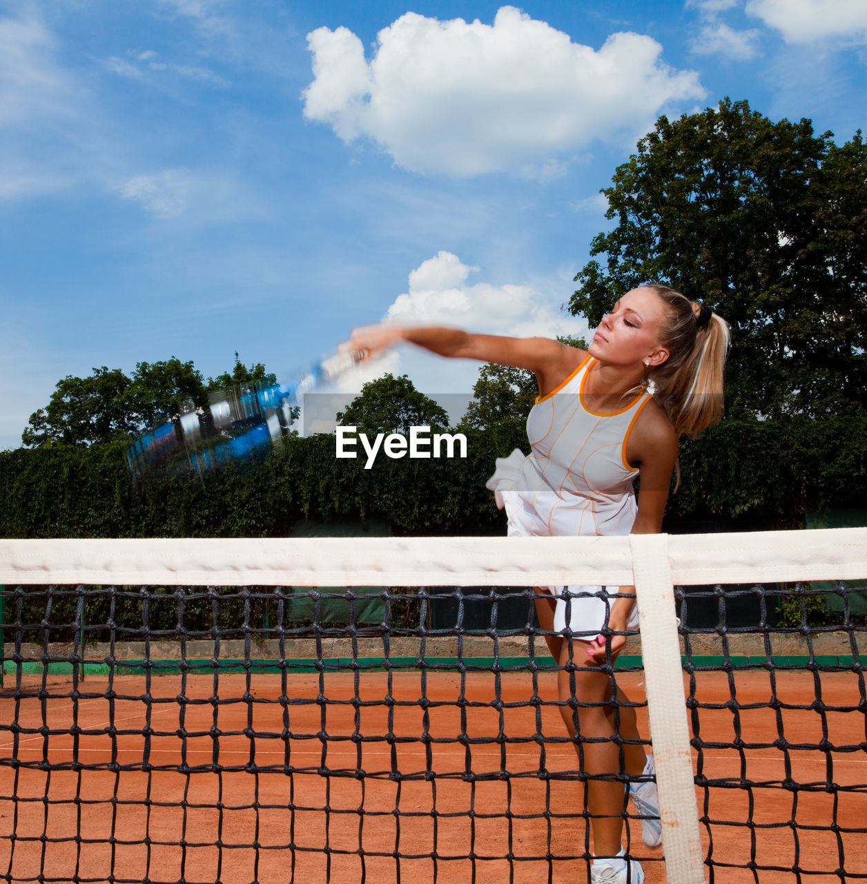 one person, child, lifestyles, blond hair, girls, sport, childhood, women, real people, sky, day, cloud - sky, tree, females, hair, playing, leisure activity, outdoors, tennis racket, hairstyle