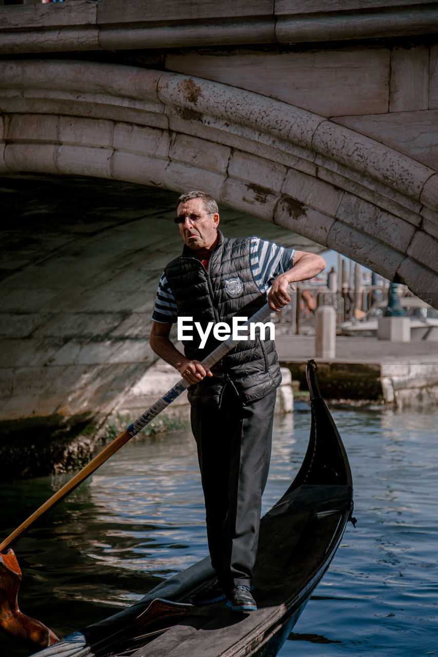 water, nautical vessel, one person, front view, standing, transportation, canal, men, mode of transportation, real people, males, architecture, holding, adult, day, lifestyles, nature, mature adult, gondola - traditional boat, mature men, outdoors, bridge - man made structure