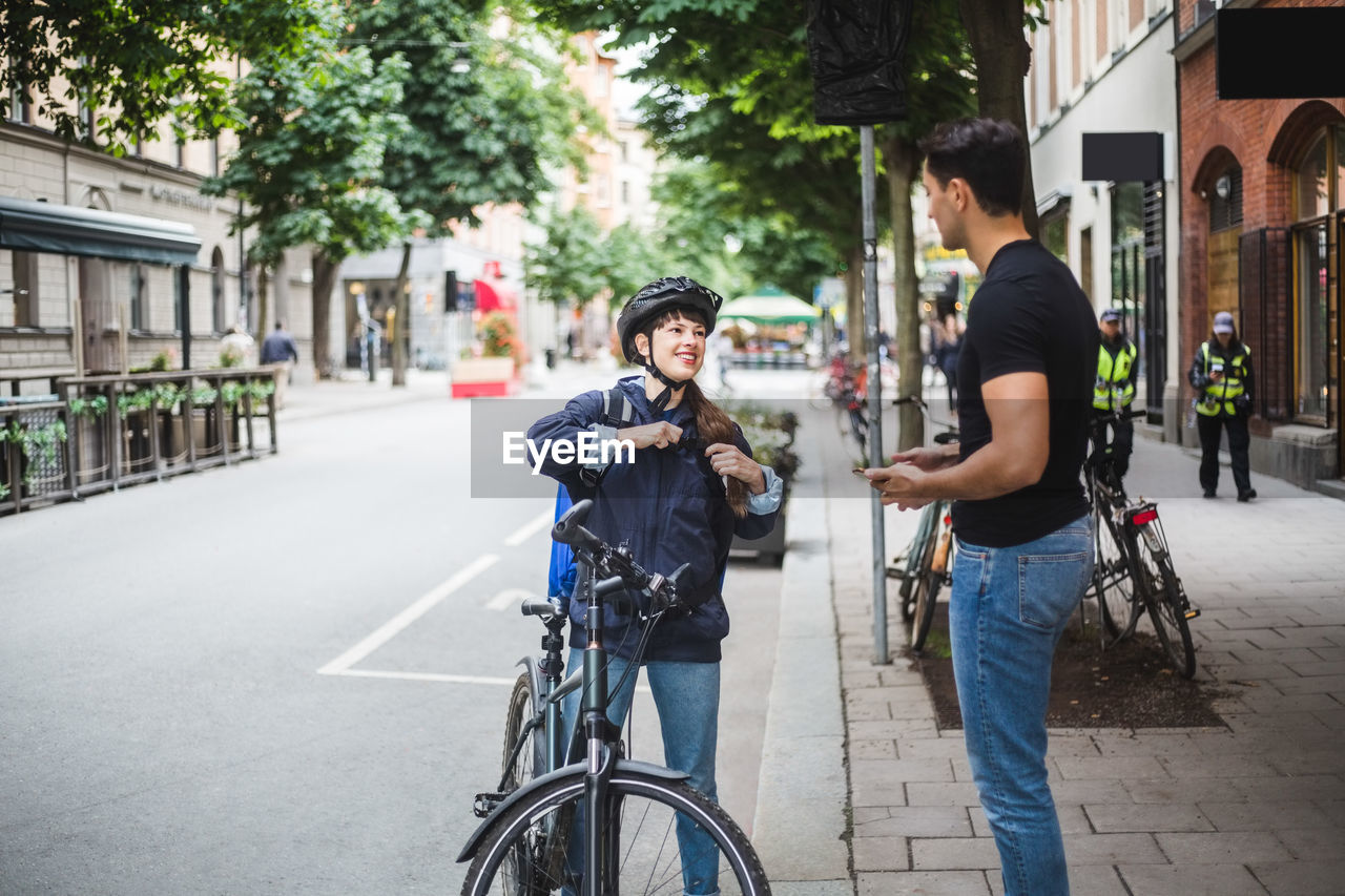 bicycle, transportation, city, street, lifestyles, real people, two people, men, architecture, leisure activity, casual clothing, activity, mid adult, building exterior, sport, city life, people, togetherness, young adult, day, city street, riding, outdoors