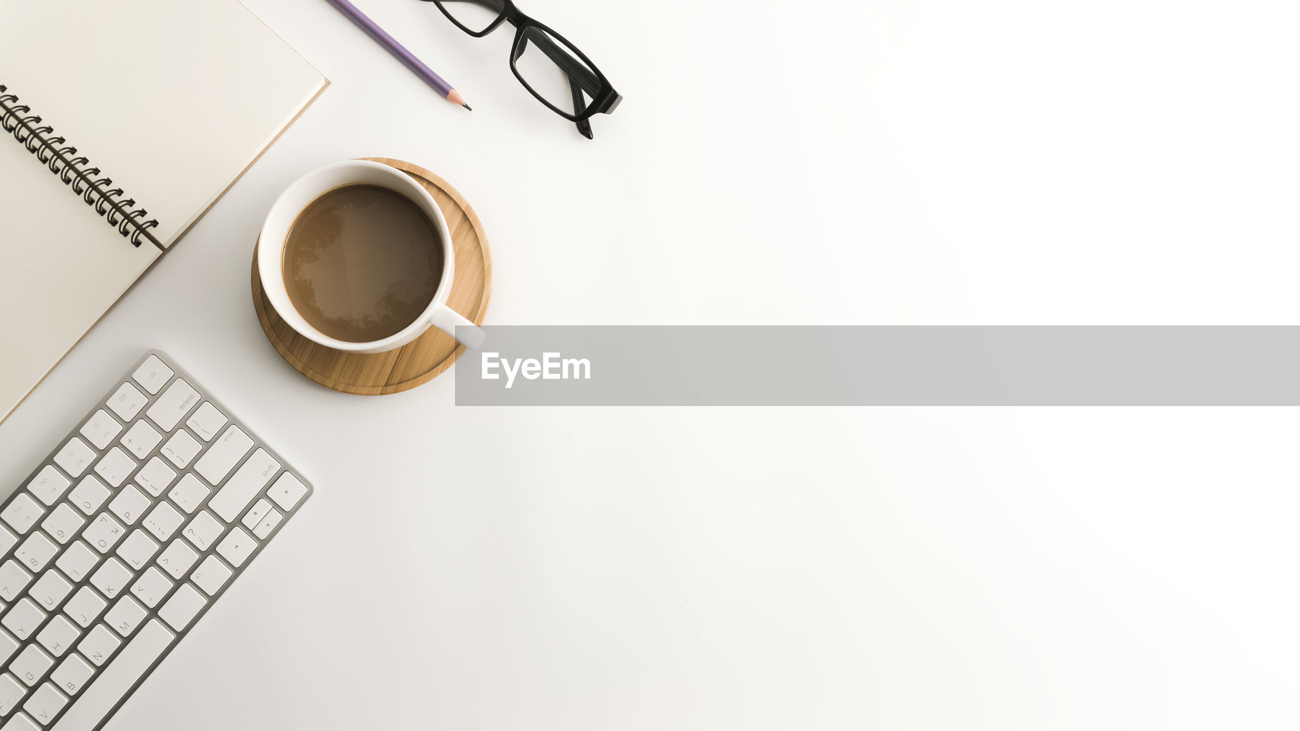 High angle view of coffee and keyboard on white background