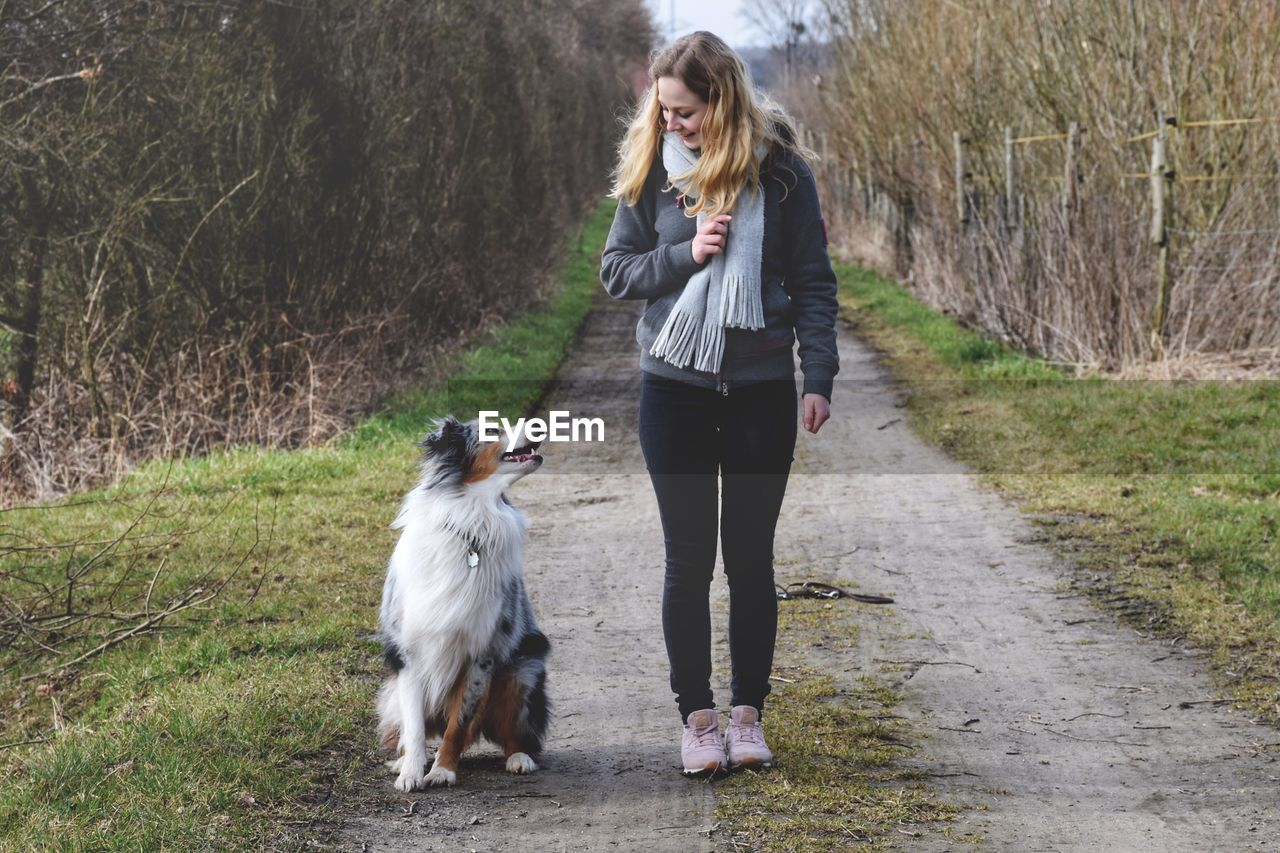 mammal, one animal, full length, domestic animals, canine, dog, domestic, pets, one person, real people, tree, plant, young adult, front view, young women, vertebrate, women, hair, hairstyle, outdoors, pet owner, warm clothing