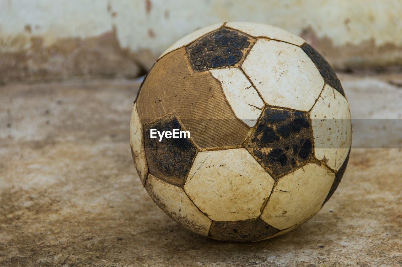 ball, soccer ball, soccer, sports equipment, sport, close-up, team sport, no people, focus on foreground, sphere, single object, day, old, outdoors, still life, damaged, dirt, shape, run-down, geometric shape, concrete
