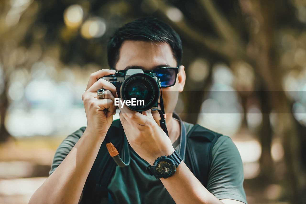 one person, focus on foreground, photography themes, camera - photographic equipment, real people, technology, photographing, activity, portrait, front view, holding, young men, lifestyles, leisure activity, headshot, young adult, casual clothing, occupation, photographic equipment, photographer, digital camera, outdoors, obscured face