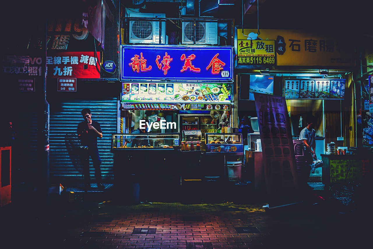 text, communication, illuminated, night, real people, built structure, city, architecture, group of people, store, non-western script, commercial sign, advertisement, script, building exterior, street, sign, men, people, poster