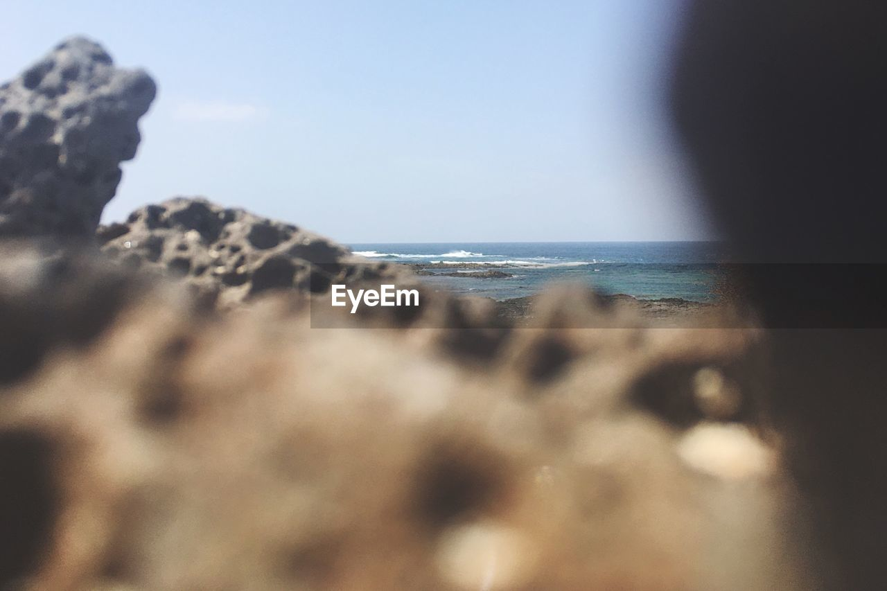 sea, horizon over water, water, nature, beauty in nature, beach, scenics, tranquility, tranquil scene, rock - object, sky, day, outdoors, no people, clear sky, pebble beach, close-up