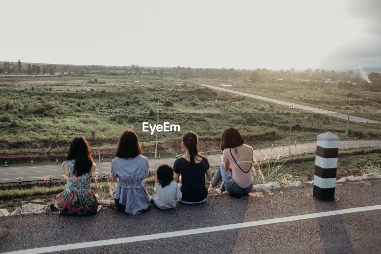 REAR VIEW OF PEOPLE SITTING ON ROAD ALONG FIELD