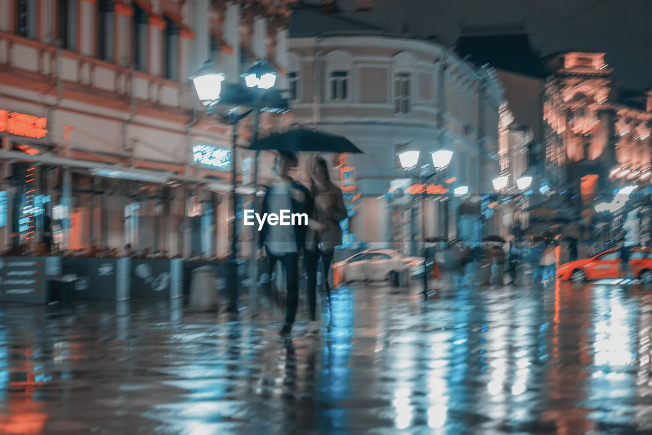architecture, illuminated, built structure, building exterior, city, real people, wet, standing, one person, walking, adult, water, night, women, street, full length, motion, lifestyles, rain, outdoors, rainy season