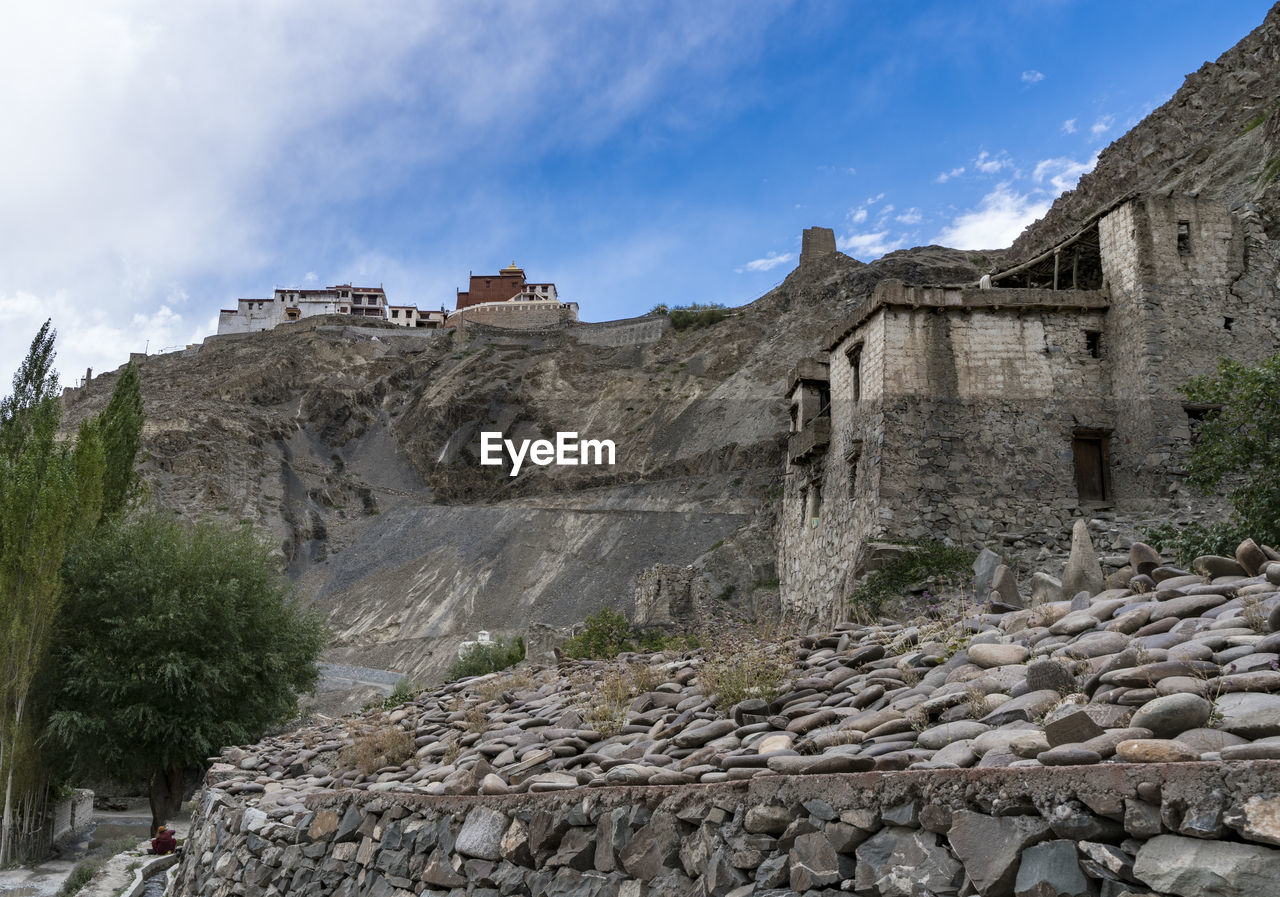 architecture, built structure, sky, building exterior, history, the past, cloud - sky, solid, building, nature, old, mountain, rock, ancient, travel destinations, plant, no people, low angle view, rock - object, travel, ancient civilization, stone wall