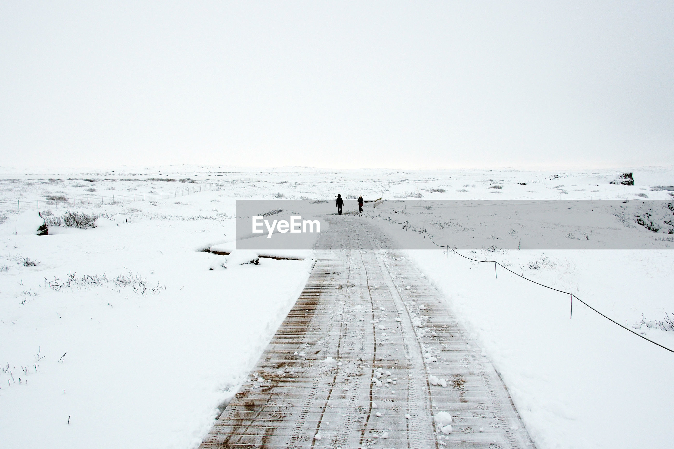 Footpath amidst snow covered field against sky