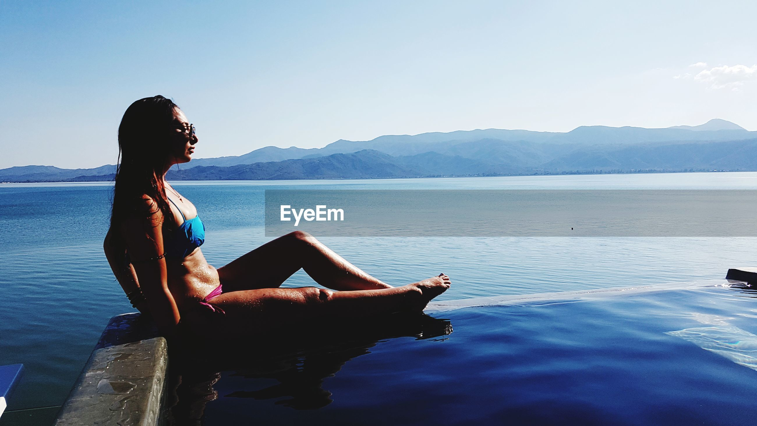Woman relaxing at infinity pool against sky