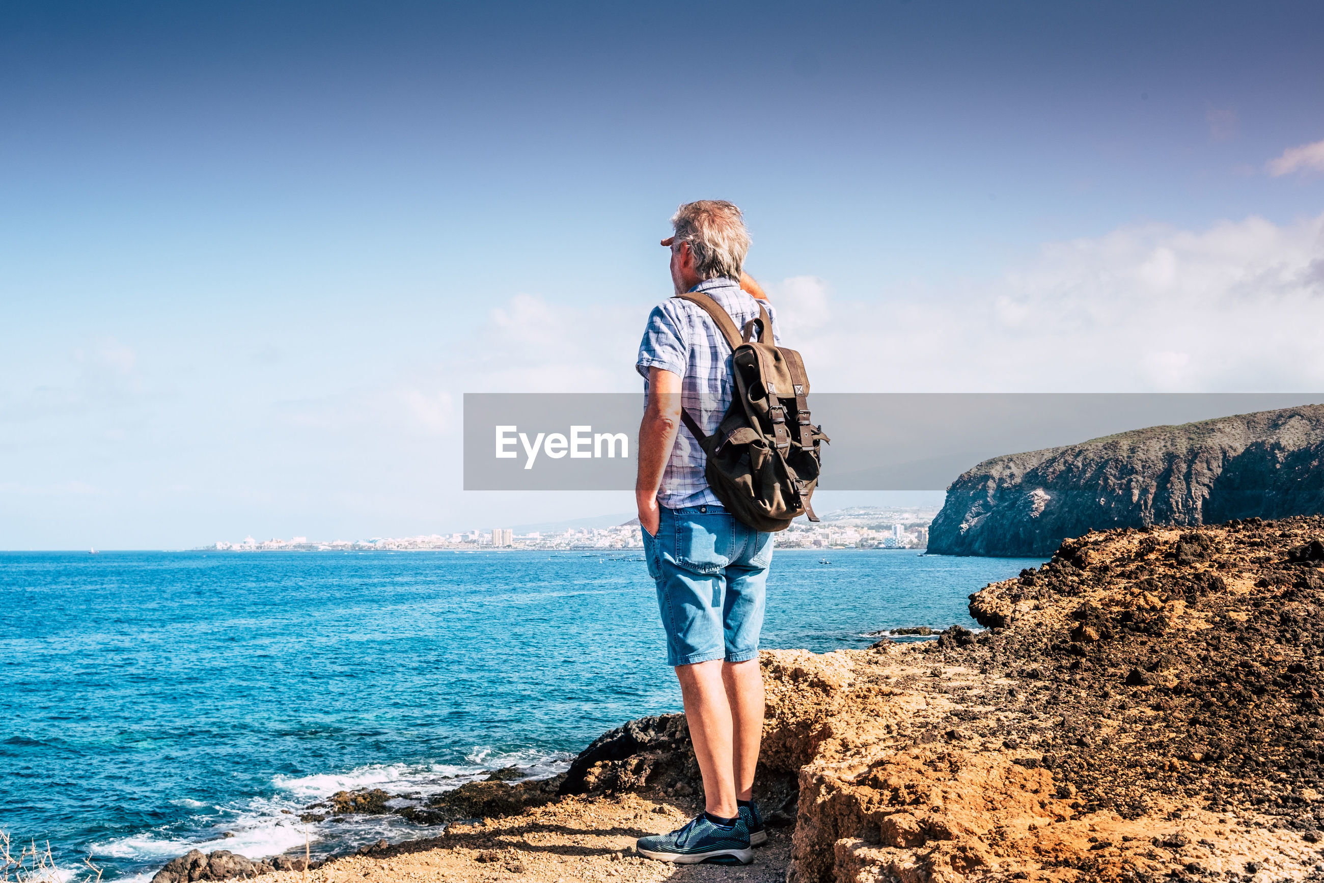 Rear view of man looking at sea while standing on rock against sky during sunny day