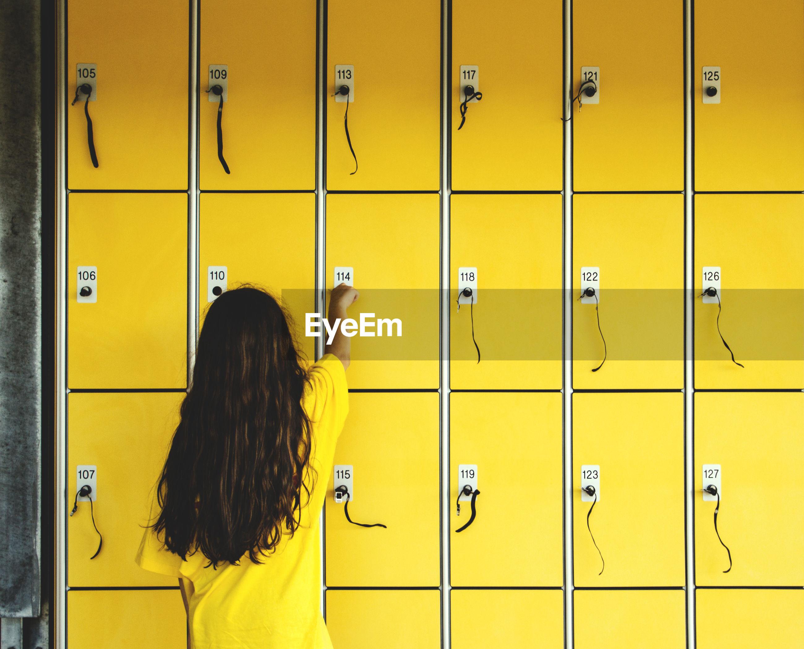 Rear view of girl using locker