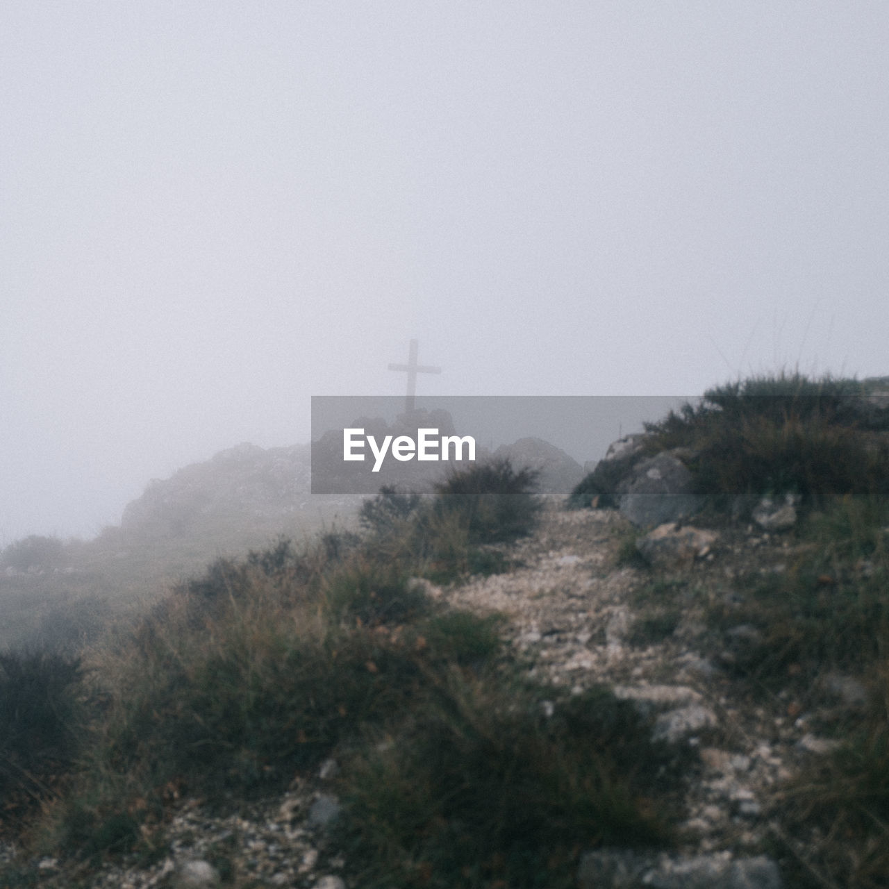 Mid distance view of cross on mountain against sky during foggy weather