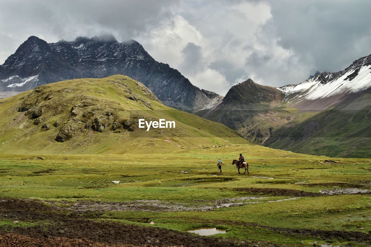 mountain, nature, mountain range, scenics, beauty in nature, cloud - sky, green color, grass, sky, real people, leisure activity, two people, lifestyles, men, tranquil scene, tranquility, landscape, outdoors, day, hiking, togetherness, friendship, people
