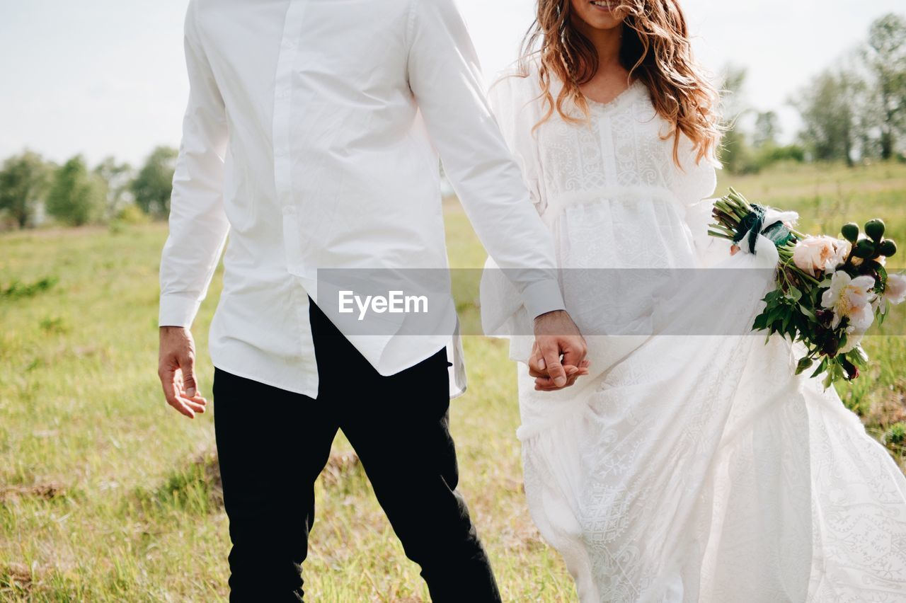 Midsection Of Couple With Holding Hands Walking On Field