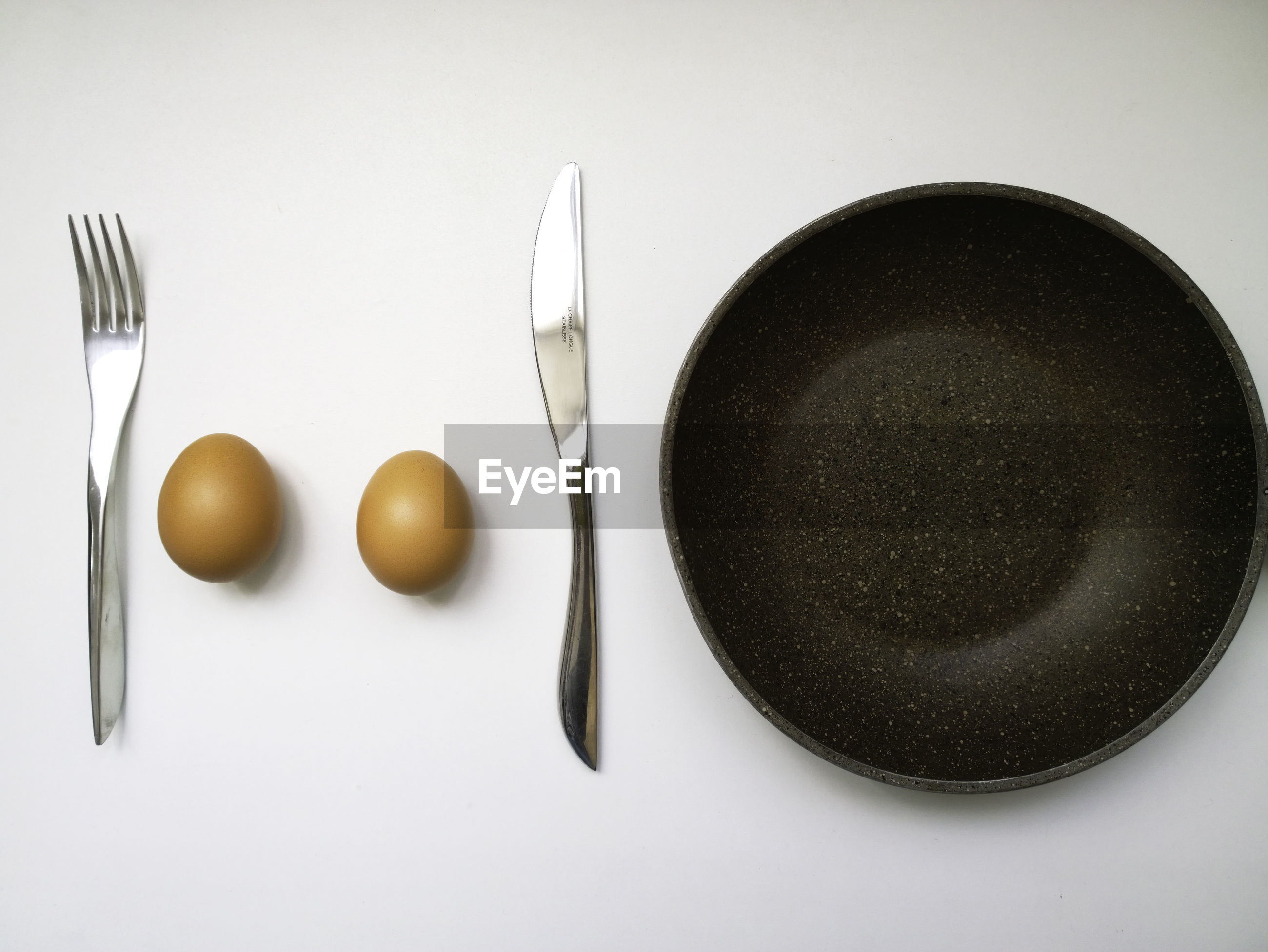 High angle view of eggs and cooking pan on white background