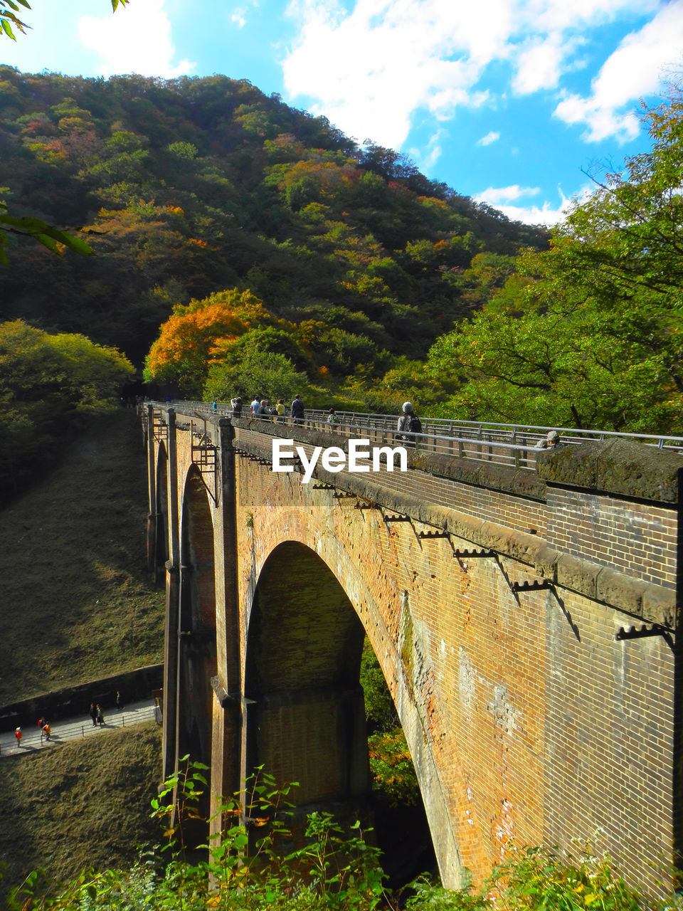 bridge, bridge - man made structure, built structure, architecture, connection, plant, tree, cloud - sky, nature, sky, arch, transportation, day, water, mountain, growth, no people, outdoors, arch bridge, wall, arched