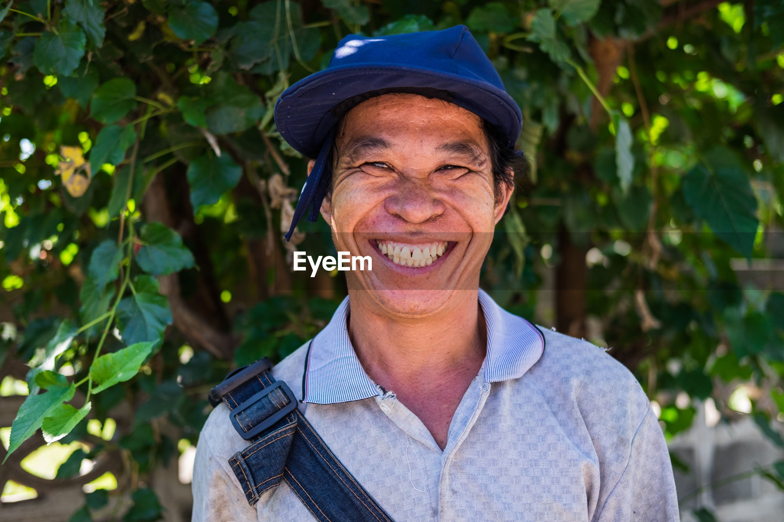 Close-up portrait of smiling man against trees