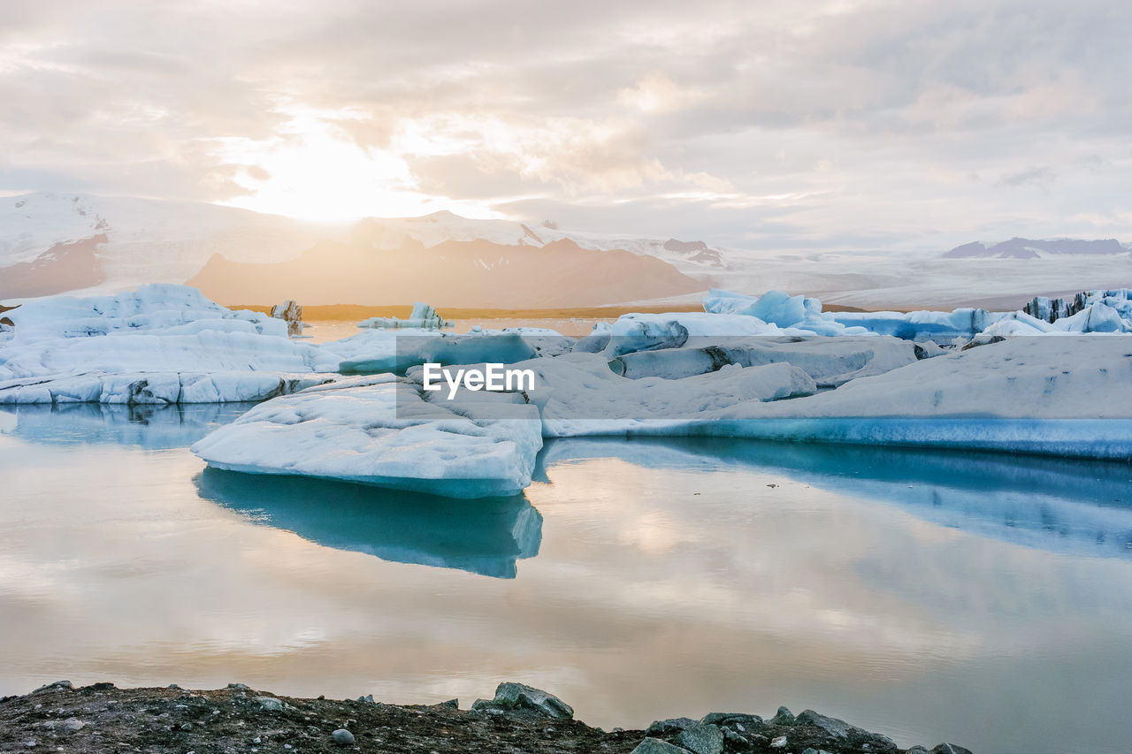 Icebergs Melting In Calm Lake Against Cloudy Sky