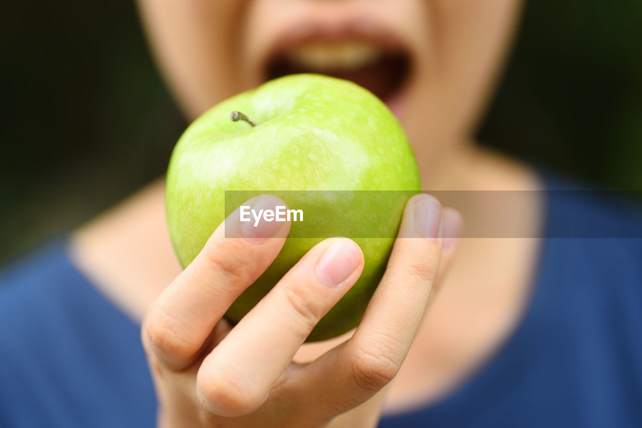 Midsection Of Woman Eating Granny Smith Apple