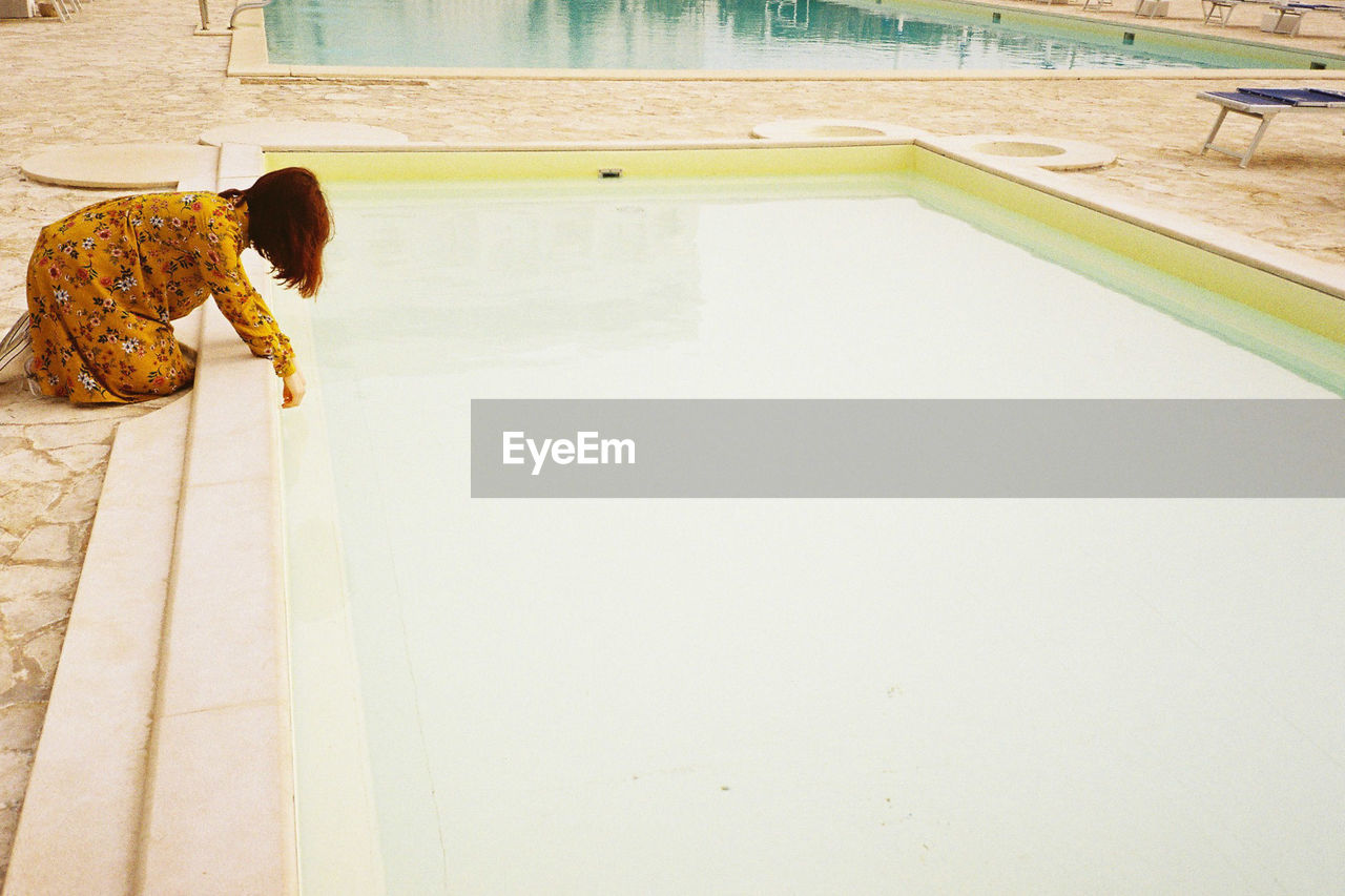 Side view of woman putting hand in swimming pool