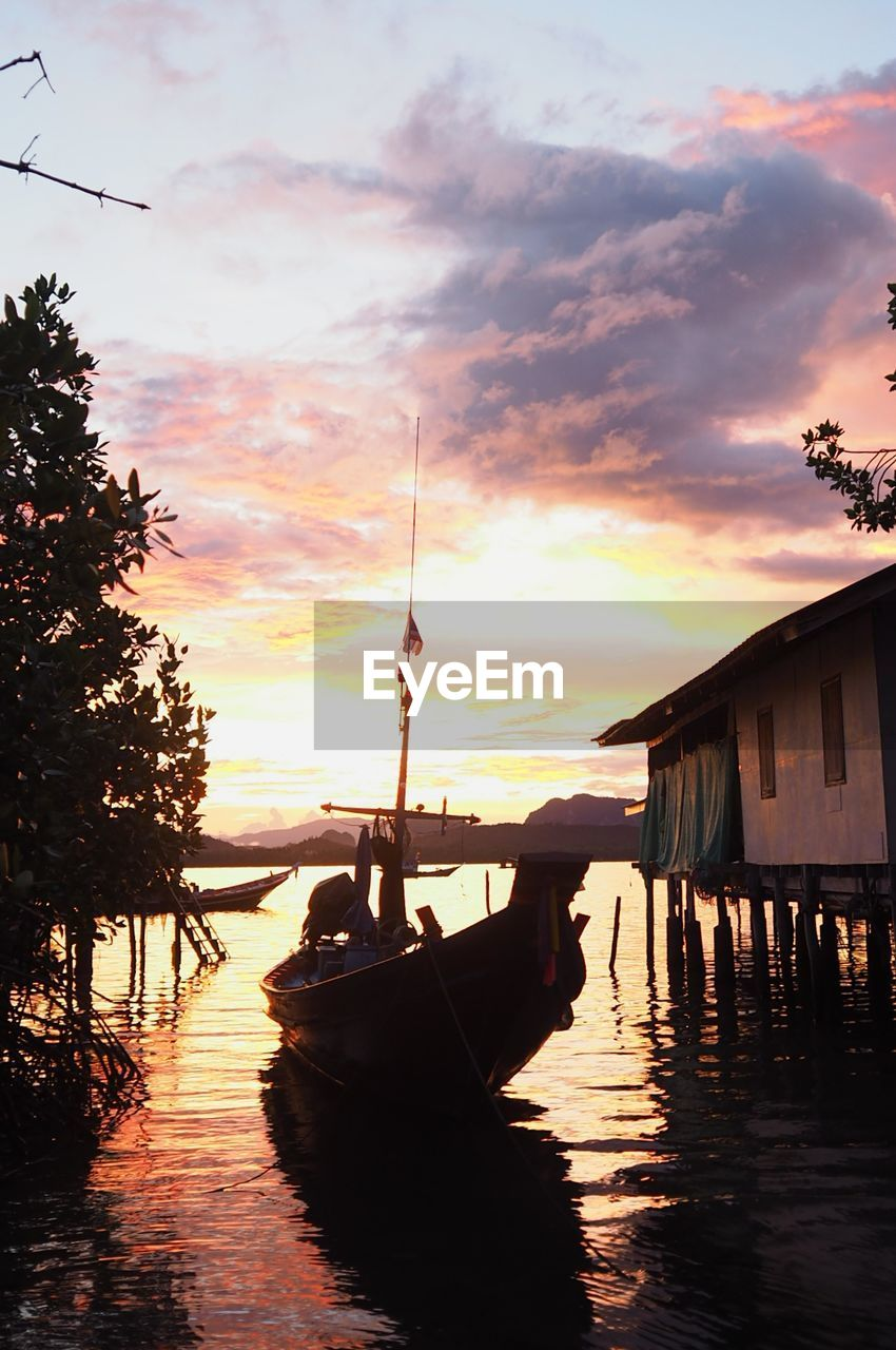 Boat moored in sea by stilt house against sky during sunset