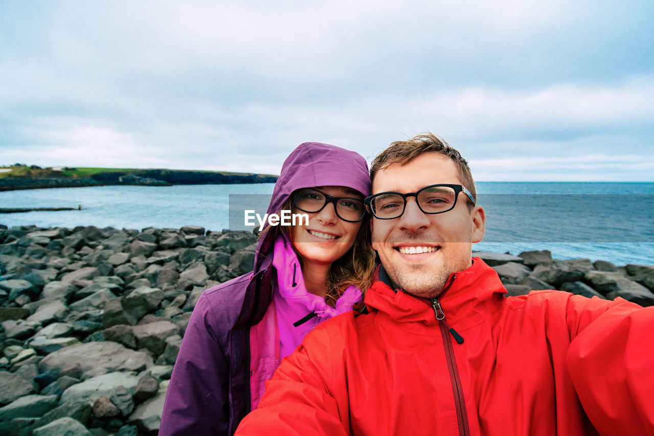 Portrait Of Smiling Couple Standing On Sea Shore Against Sky