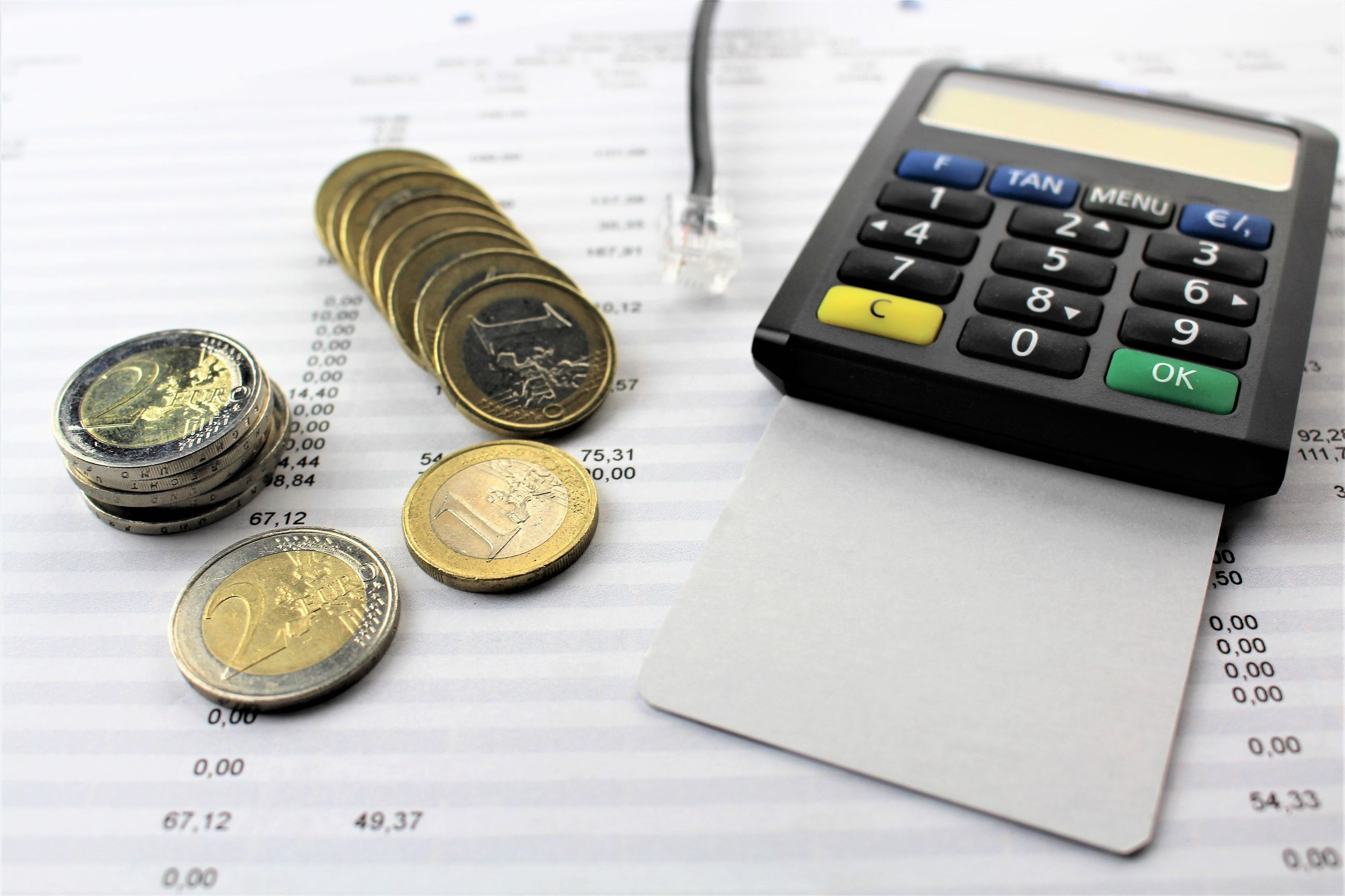 Close-up of bill with calculator and coins on table