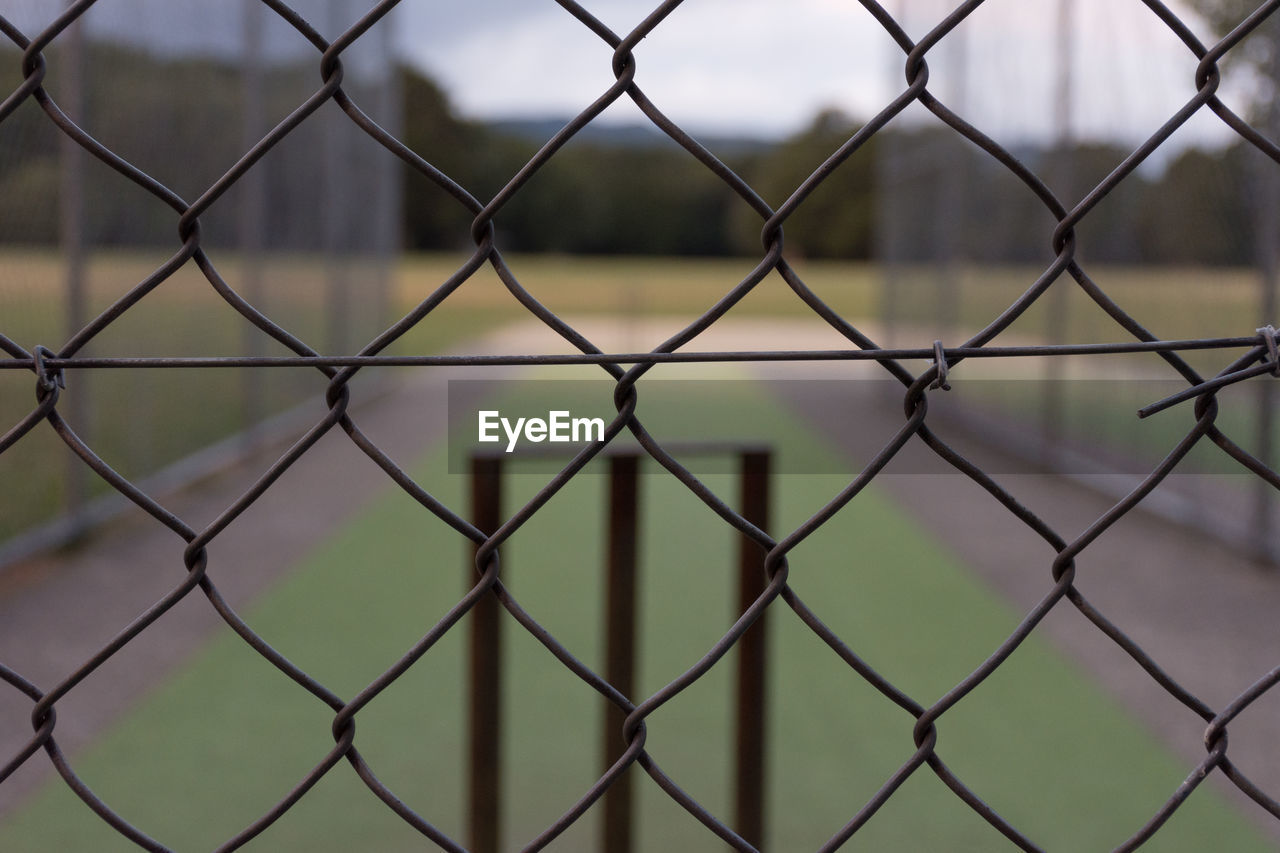 FULL FRAME SHOT OF CHAINLINK FENCE AGAINST CLOUDY SKY SEEN THROUGH METAL GRATE