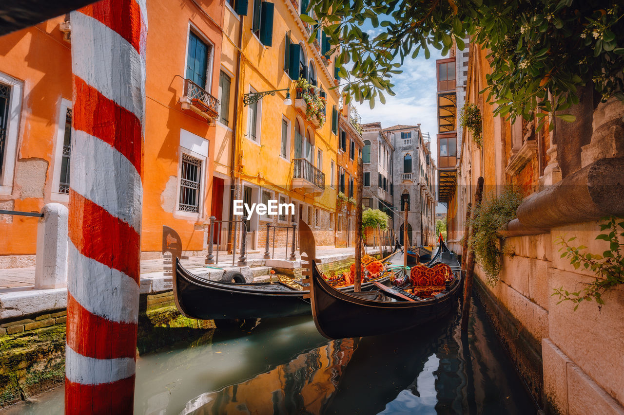 nautical vessel, water, built structure, building exterior, transportation, architecture, mode of transportation, canal, nature, day, moored, no people, building, tree, plant, reflection, outdoors, city, sunlight, gondola - traditional boat