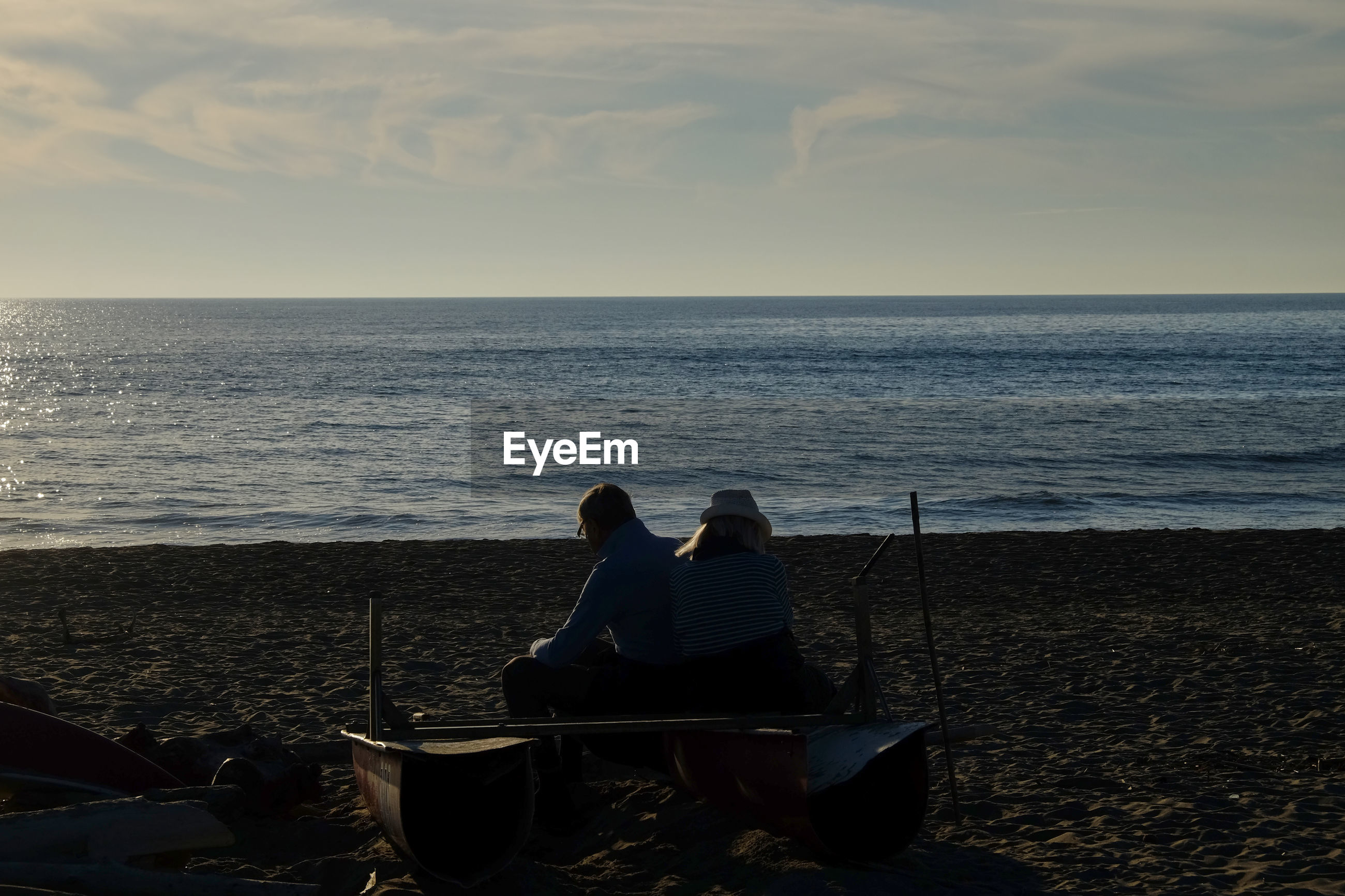 REAR VIEW OF TWO PEOPLE SITTING ON BEACH