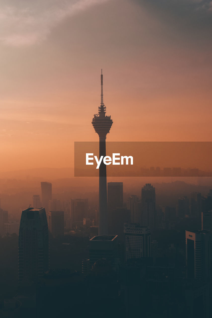 architecture, built structure, building exterior, sky, sunset, city, building, tall - high, tower, travel destinations, orange color, cityscape, no people, office building exterior, nature, travel, tourism, silhouette, skyscraper, outdoors, modern, spire, romantic sky