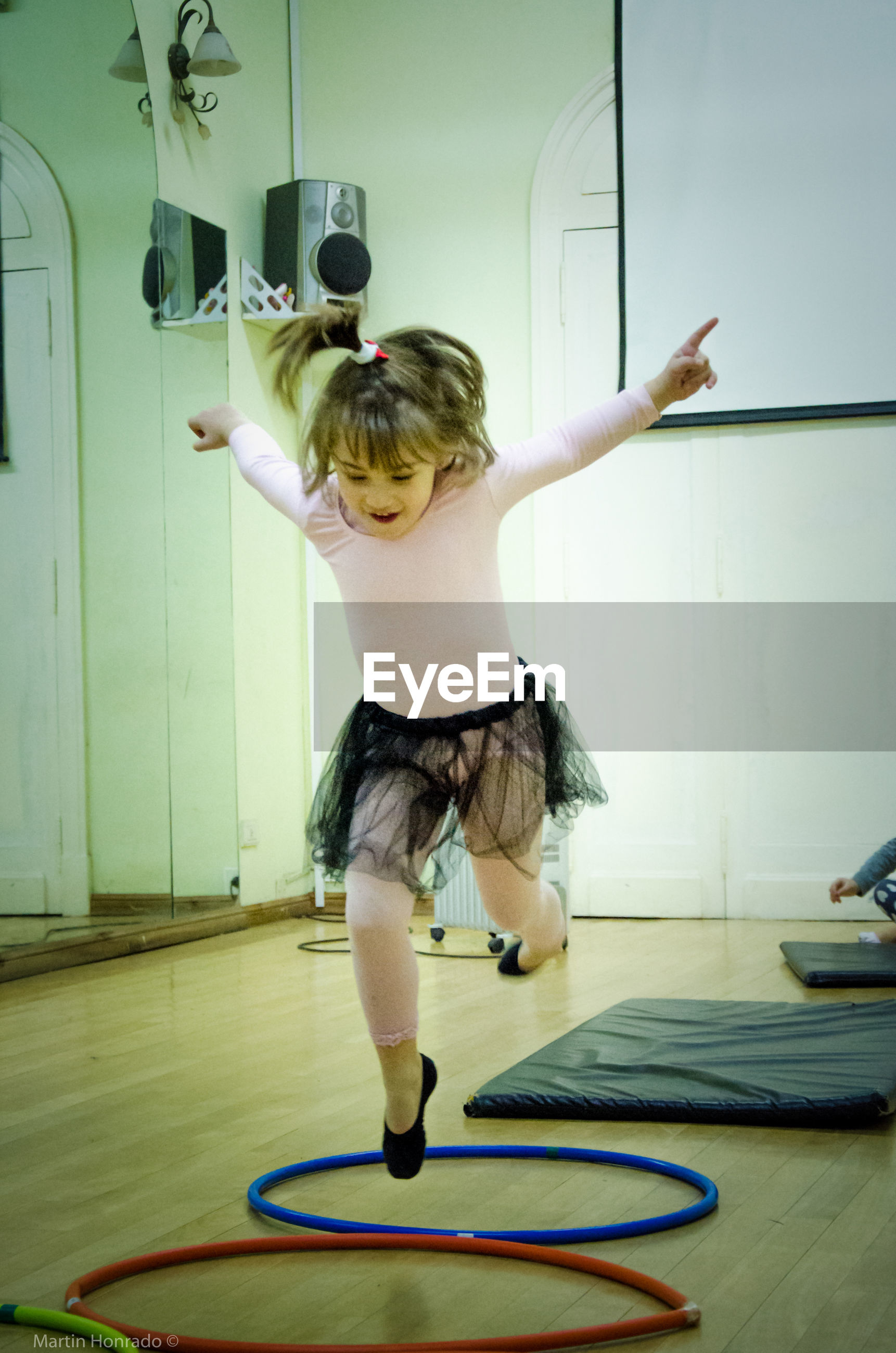 Front view of girl jumping over hoops in dance studio