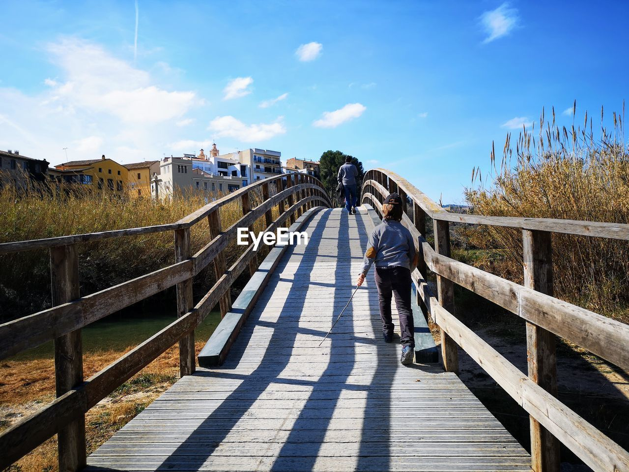 real people, one person, architecture, sky, built structure, lifestyles, railing, the way forward, direction, nature, leisure activity, full length, day, casual clothing, standing, sunlight, bridge, shadow, women, footbridge, bridge - man made structure, outdoors, diminishing perspective