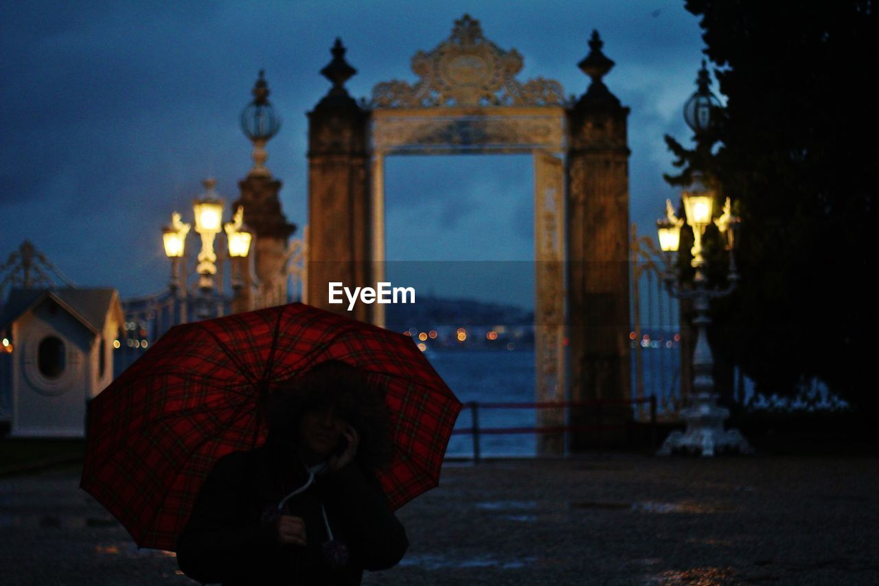 Person with umbrella during rain at dusk