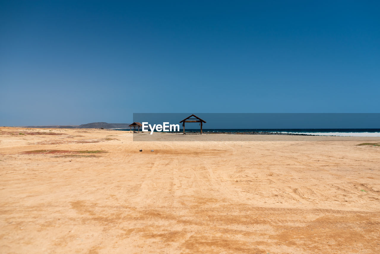 land, sky, scenics - nature, horizon, copy space, sea, beauty in nature, clear sky, nature, beach, day, blue, sand, water, environment, tranquil scene, horizon over water, tranquility, outdoors, no people
