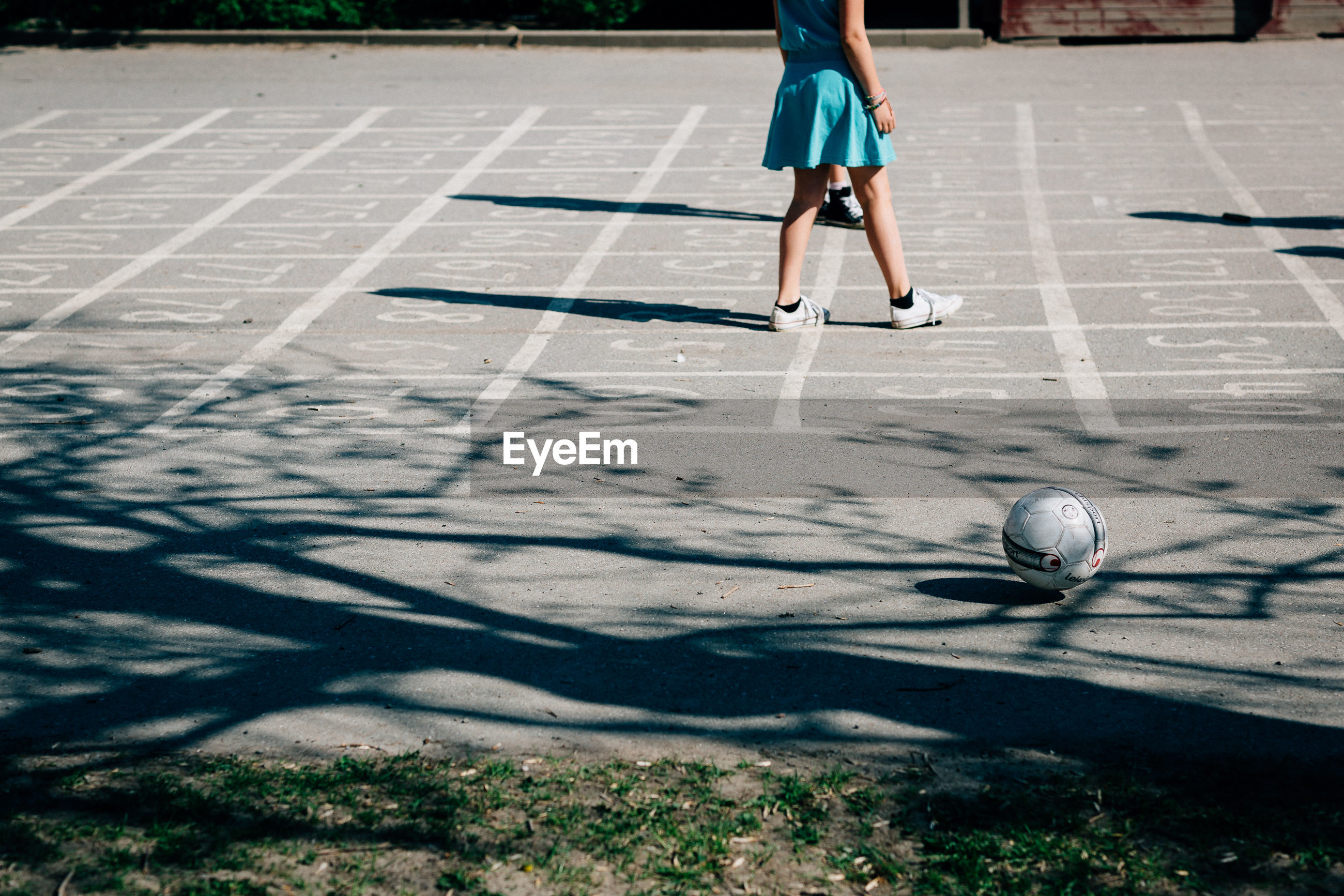 Low section of woman by soccer ball on playing field