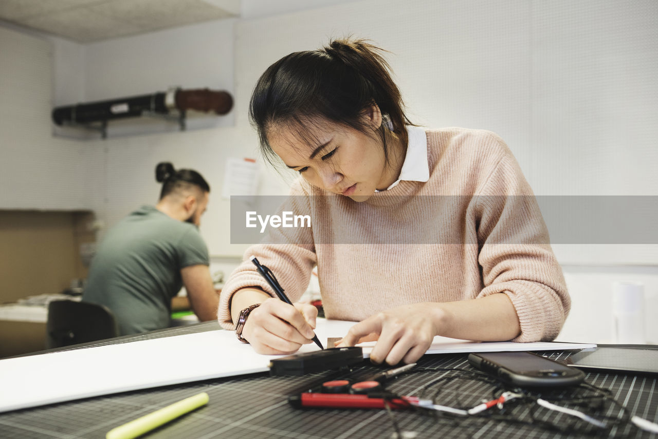 Female engineer working on paper at table in workshop