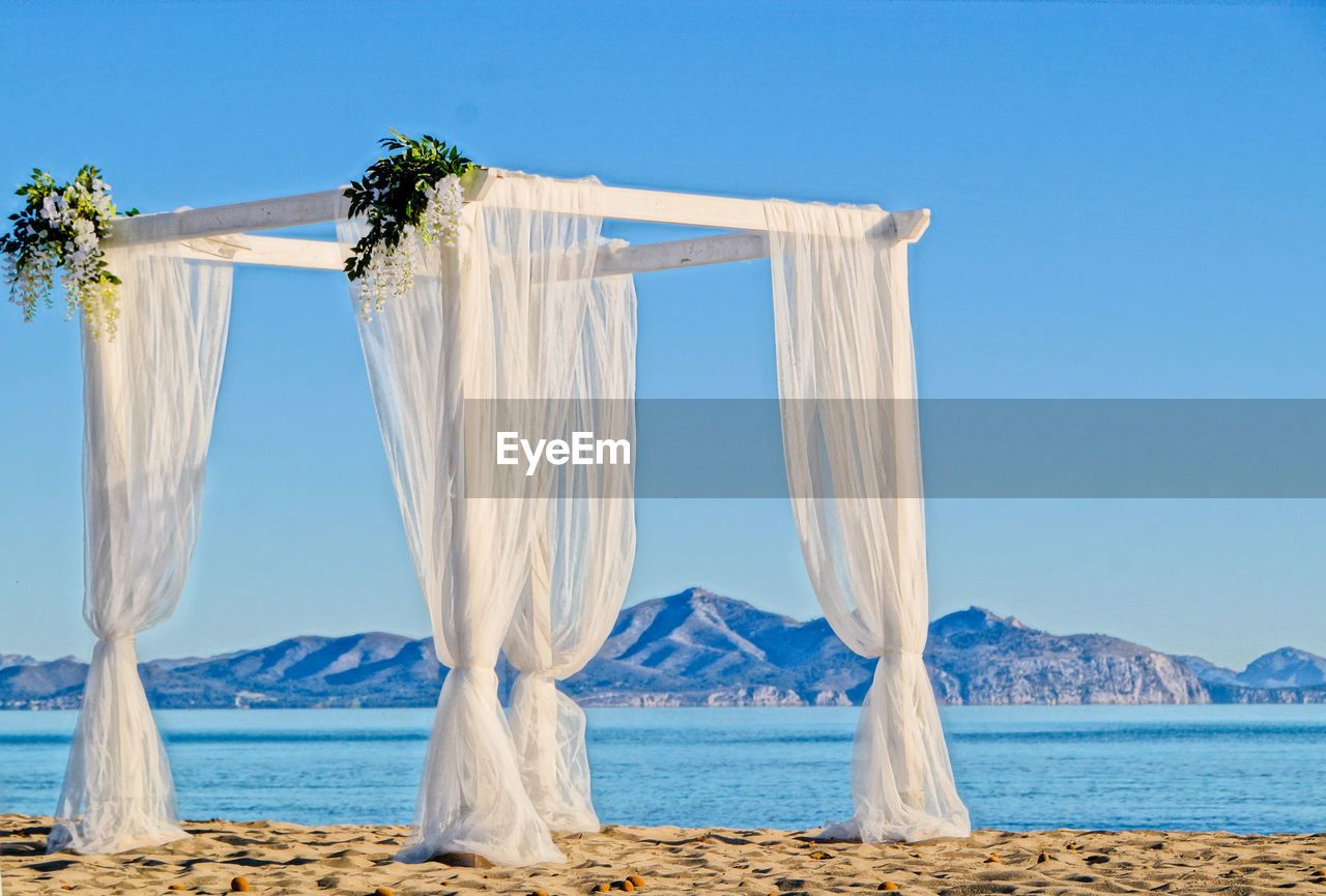 sky, water, sea, land, nature, beach, blue, clear sky, scenics - nature, beauty in nature, day, mountain, wedding, no people, tranquil scene, celebration, event, tranquility, outdoors, flower arrangement, wedding ceremony, bouquet