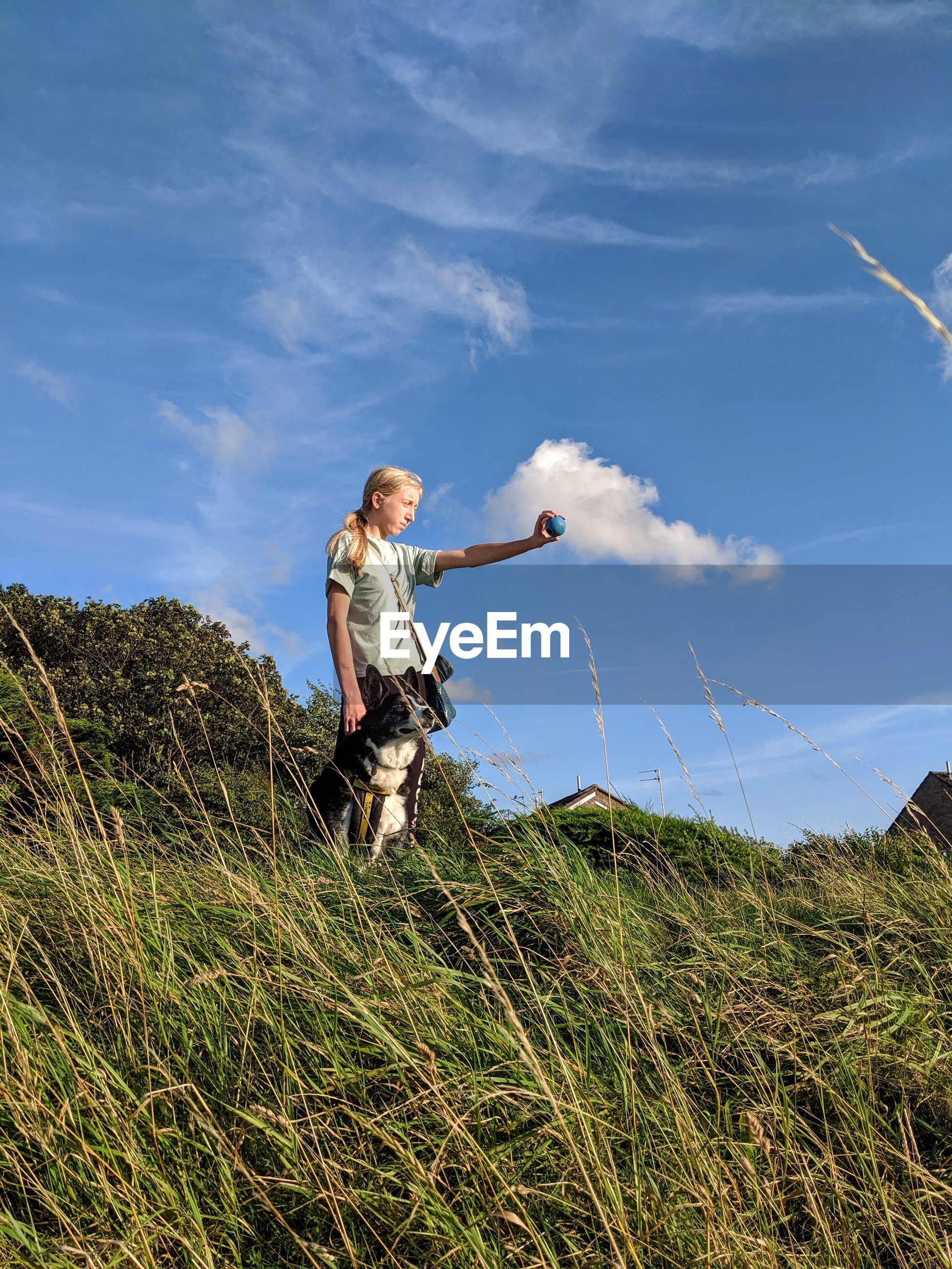 Low angle view of teenage girl standing by dog against sky