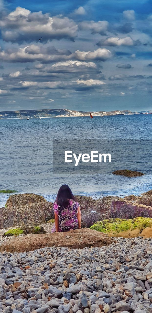 water, sea, real people, sky, beauty in nature, beach, scenics - nature, rear view, land, solid, cloud - sky, rock, lifestyles, one person, nature, rock - object, leisure activity, women, day, outdoors, looking at view