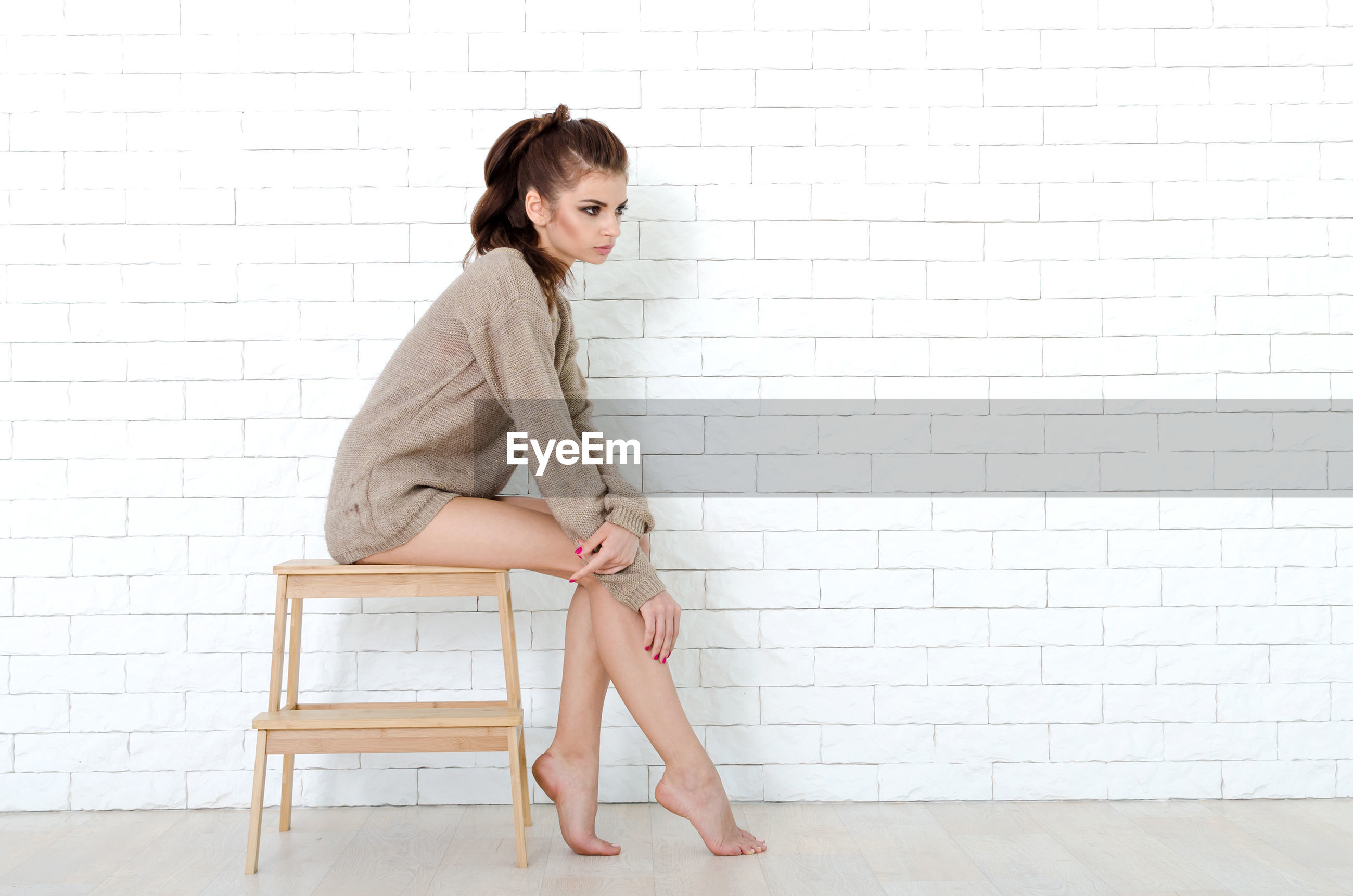 Full length of woman sitting on stool against wall