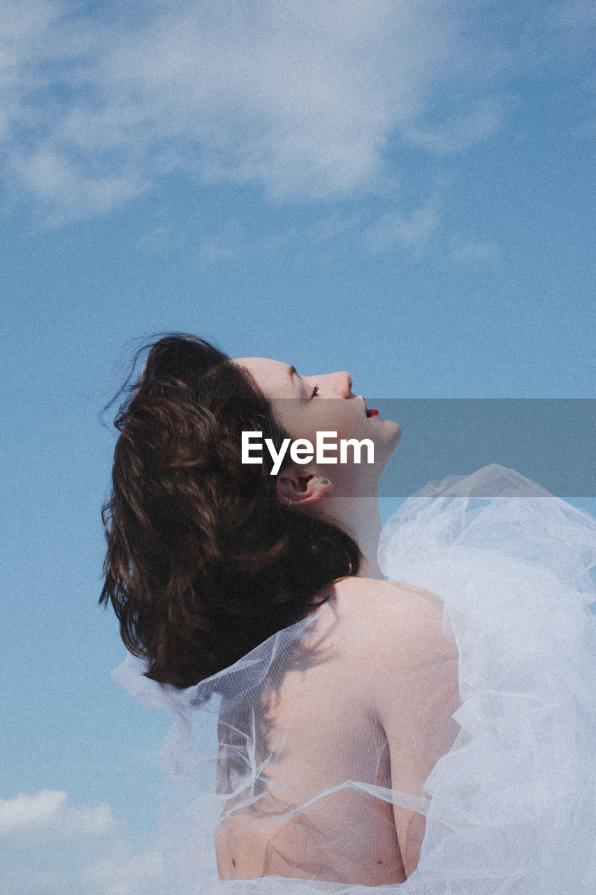 Low Angle View Of Young Woman In White Dress Against Sky