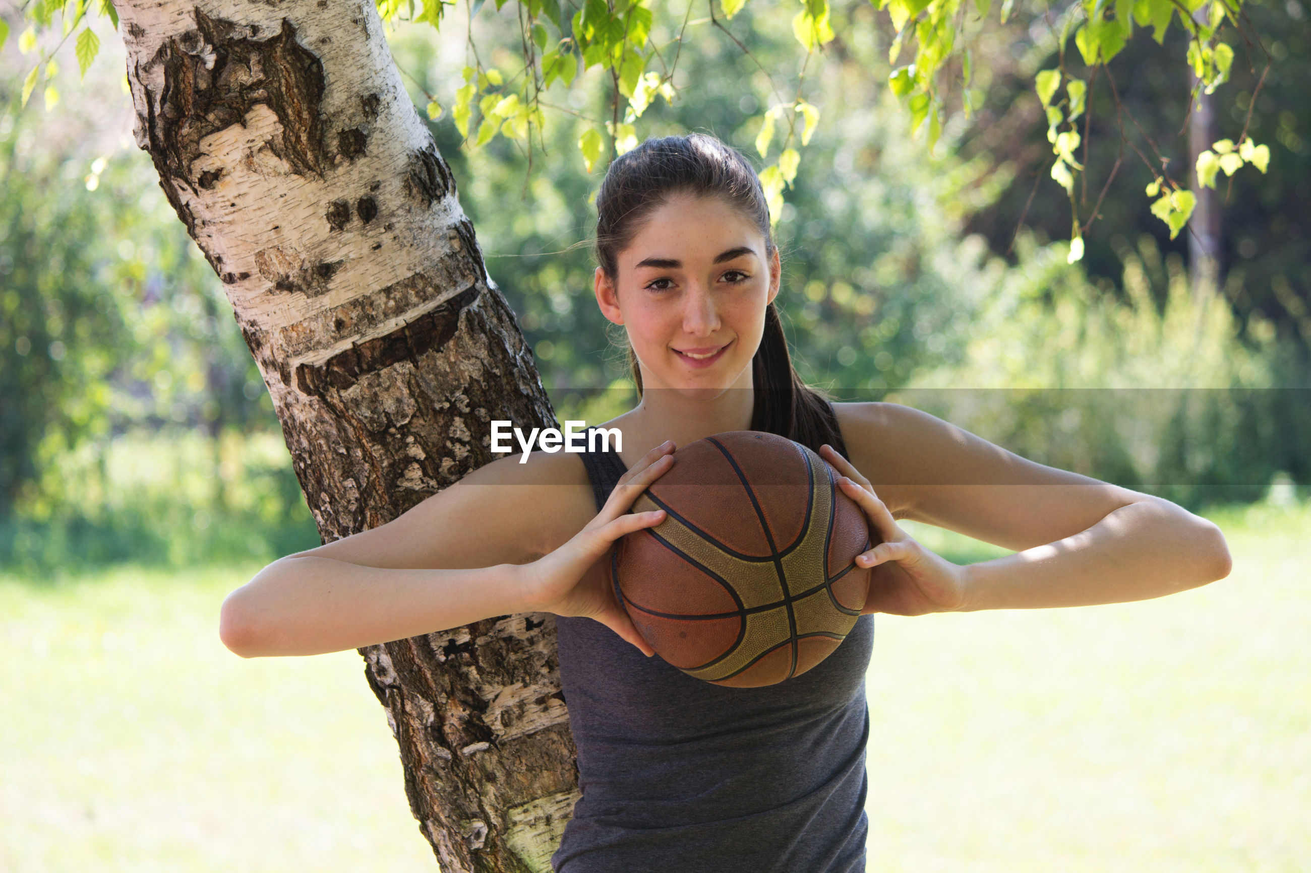 Portrait of smiling player holding basketball