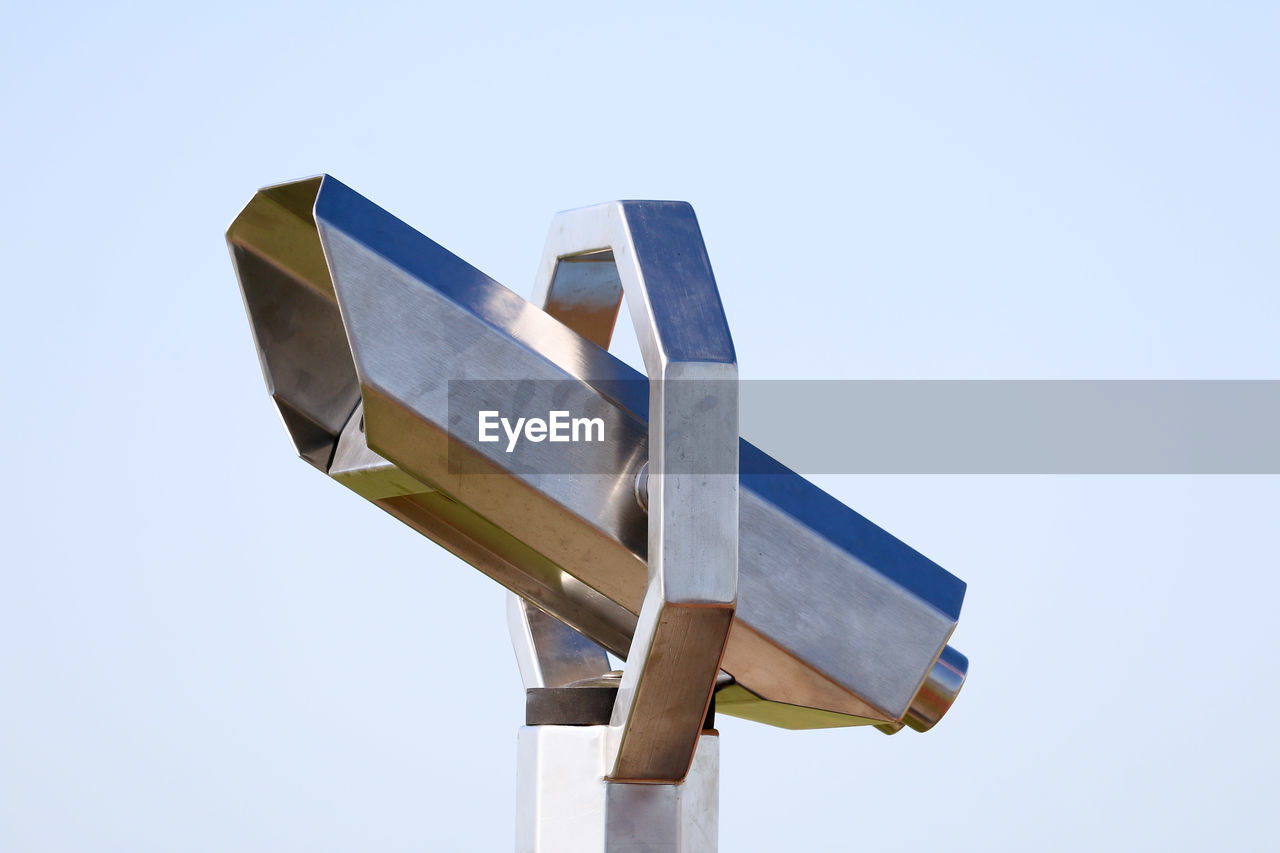 sky, low angle view, no people, blue, clear sky, day, nature, copy space, metal, outdoors, still life, shape, wood - material, sunlight, transportation, focus on foreground, white color, sign, pole, close-up, plane