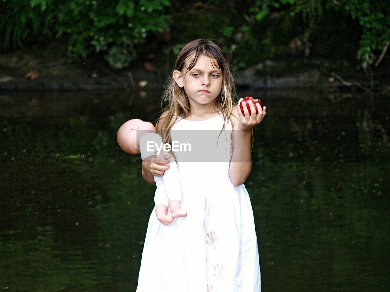 Girl Holding Doll While Eating Apple By Creek