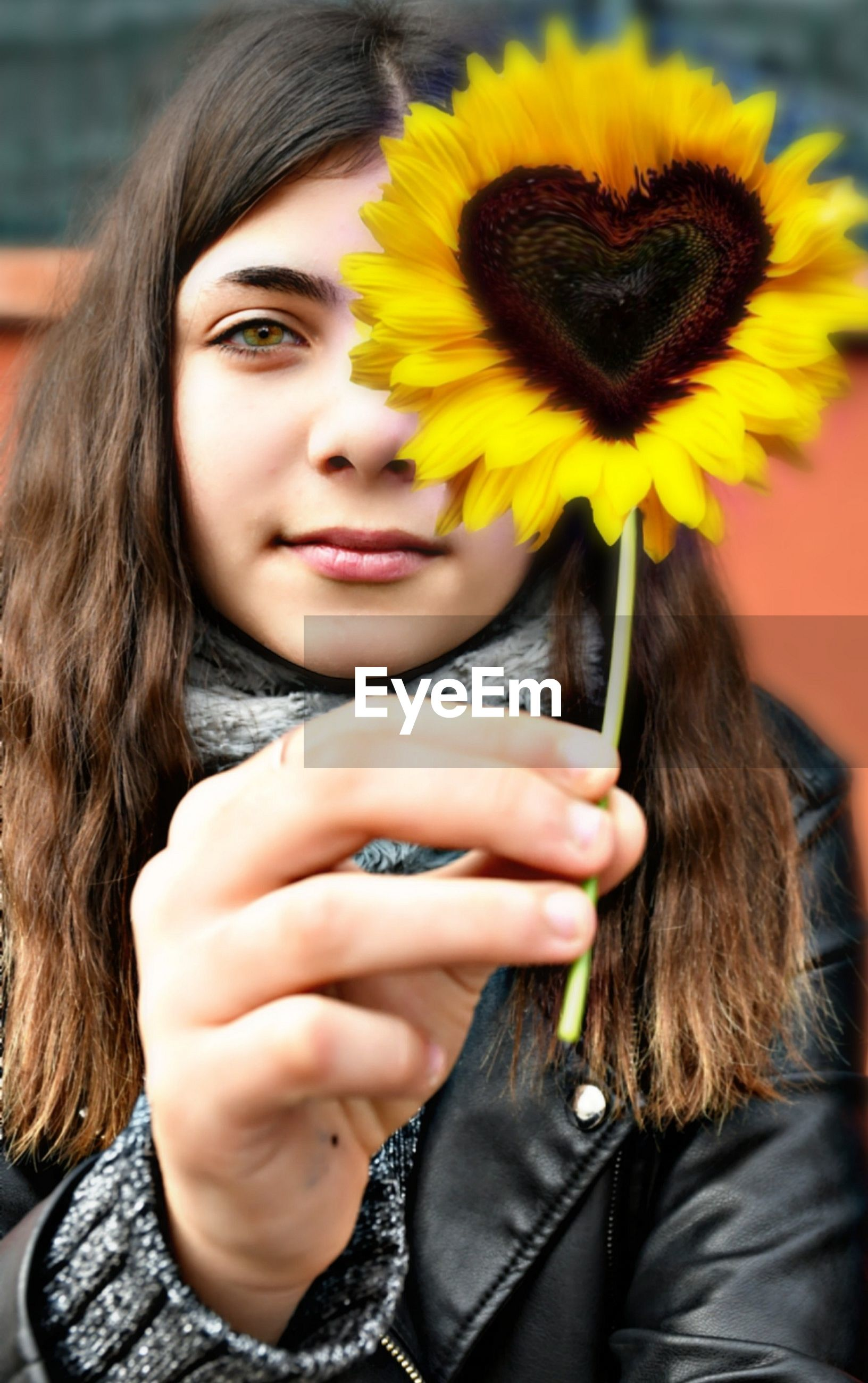 Portrait of beautiful woman holding yellow flower outdoors
